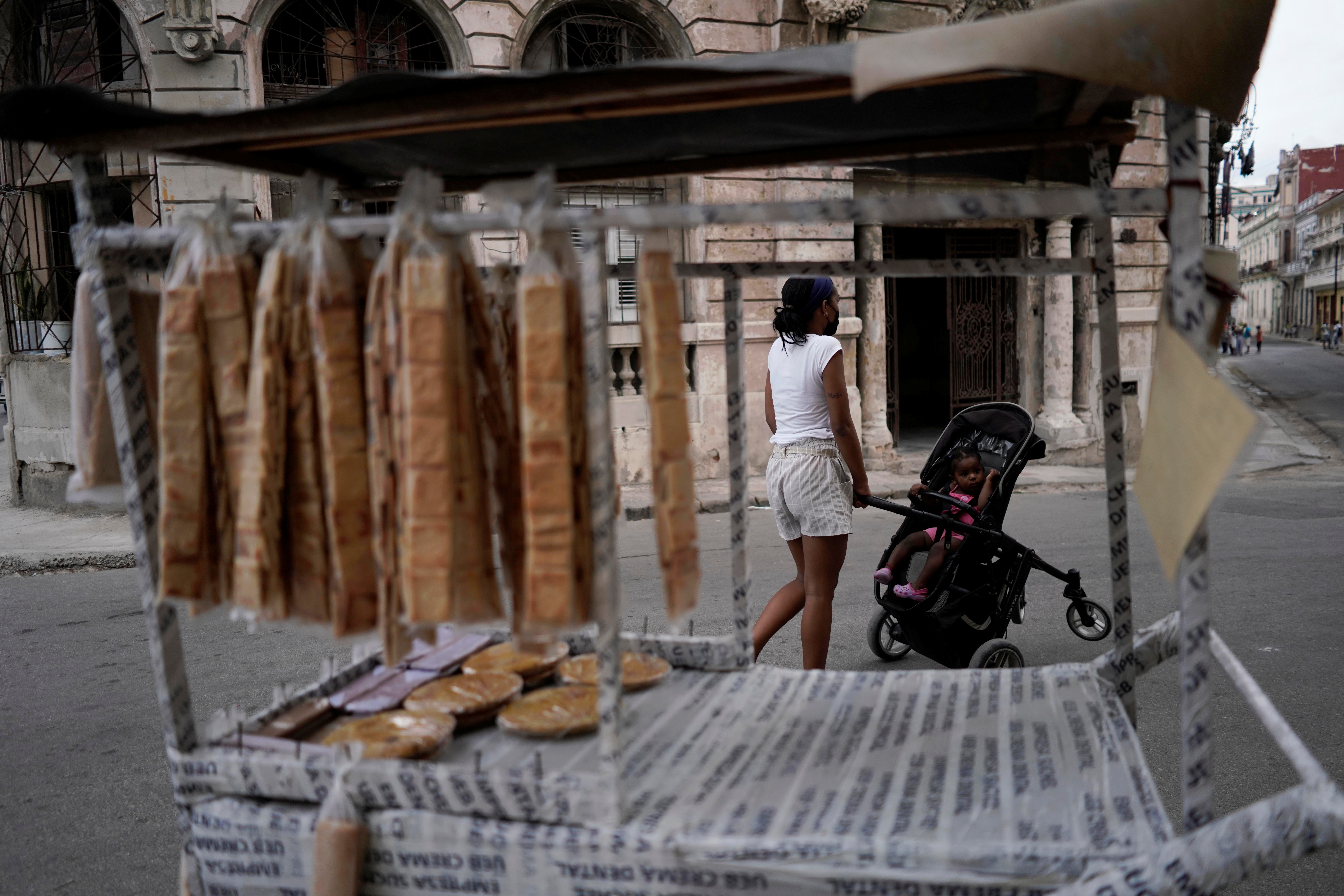 A woman walks past a cart selling biscuits in downtown Havana, Cuba, May 18, 2021. Picture taken on May 18, 2021. REUTERS/Alexandre Meneghini