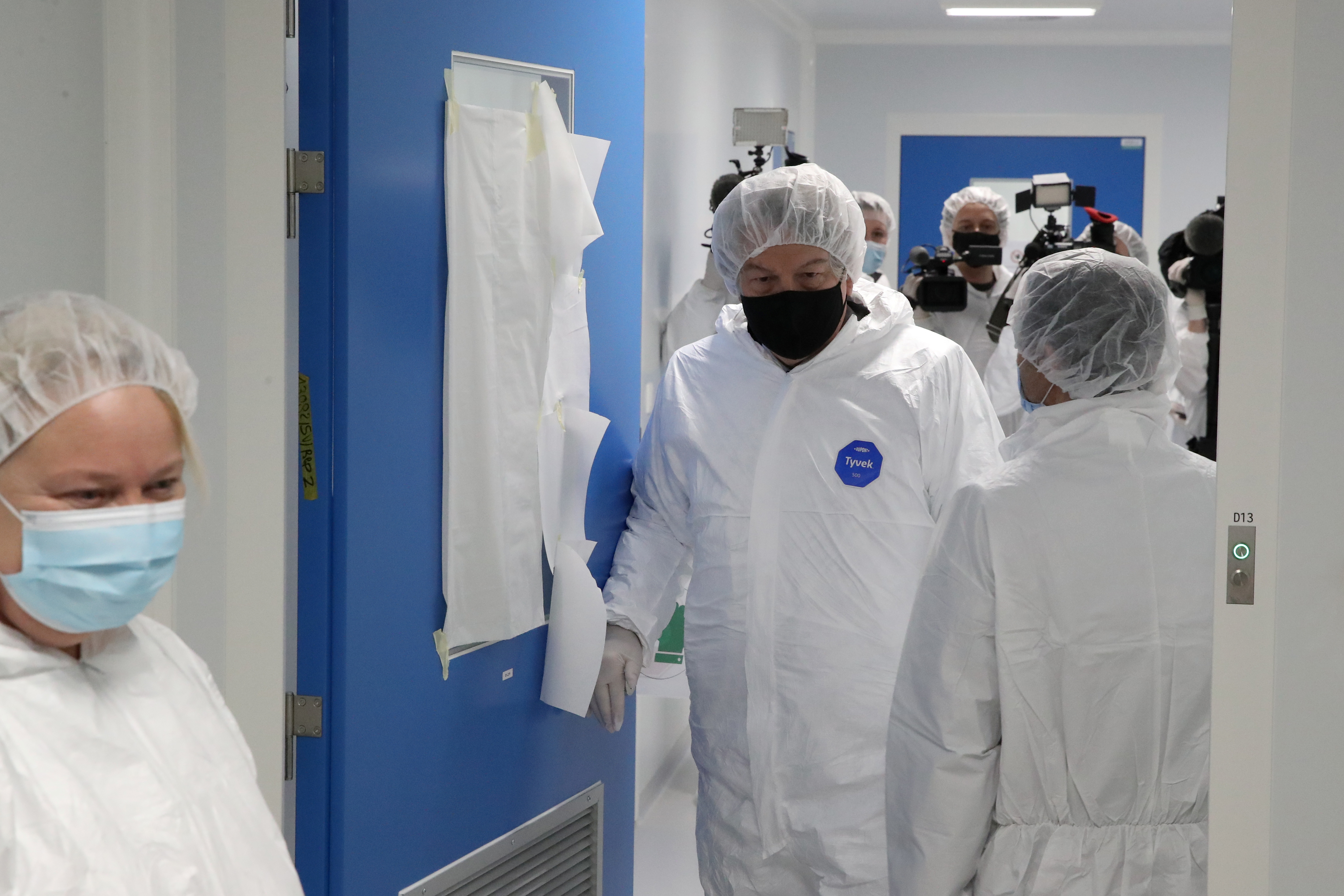 European Industry Commissioner Thierry Breton, wearing protective gear, enters a lab during a visit at the Thermo Fisher plant, former Novasep, producing COVID-19 vaccines for AstraZeneca in Seneffe, Belgium, February 10, 2021.  REUTERS/Yves Herman