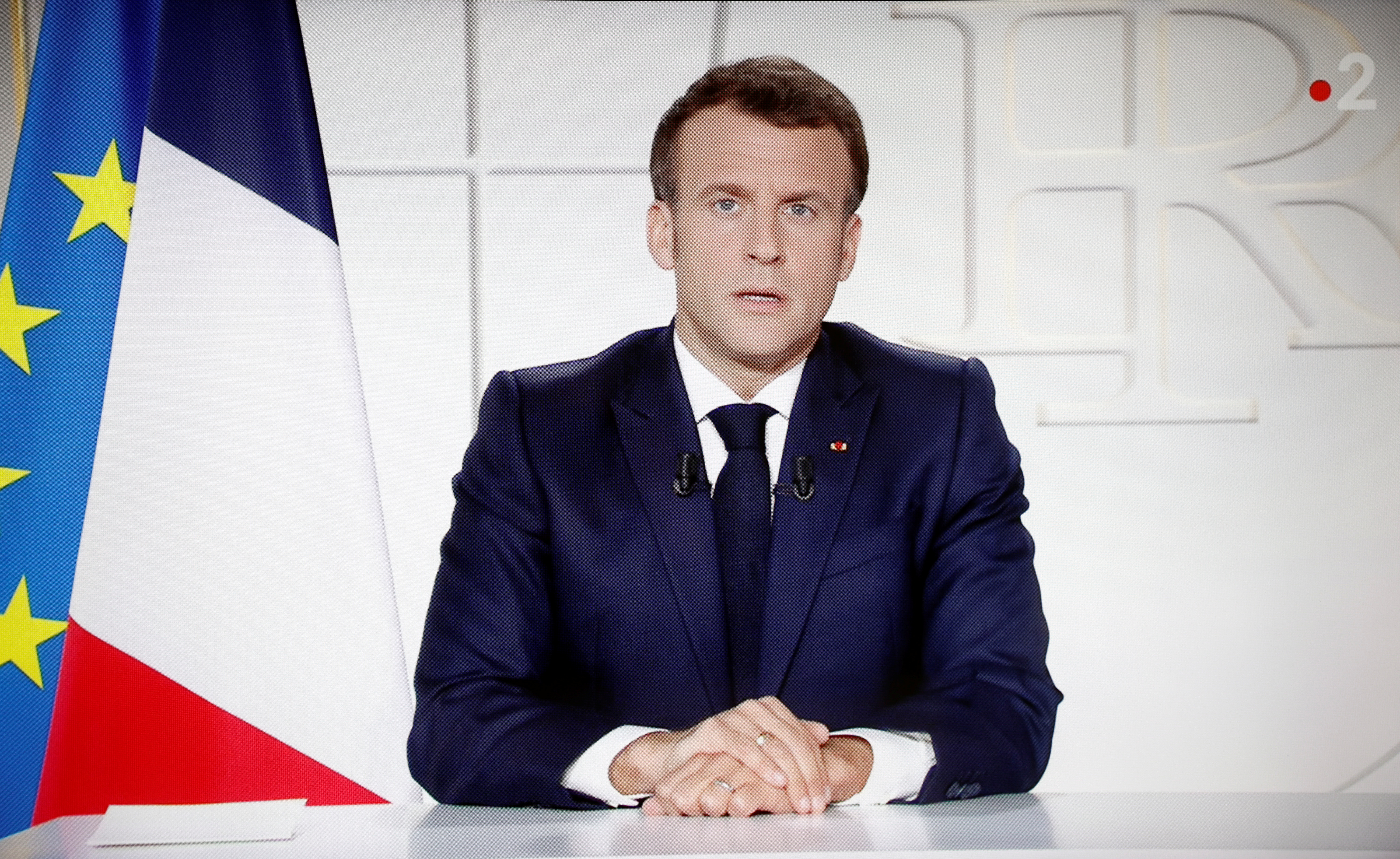 French President Emmanuel Macron is seen on a screen as he addresses the nation about the state of the coronavirus disease (COVID-19) outbreak as a fast-spreading third wave of COVID-19 infections threatens to over-run hospitals in France, March 31, 2021. REUTERS/Stephane Mahe