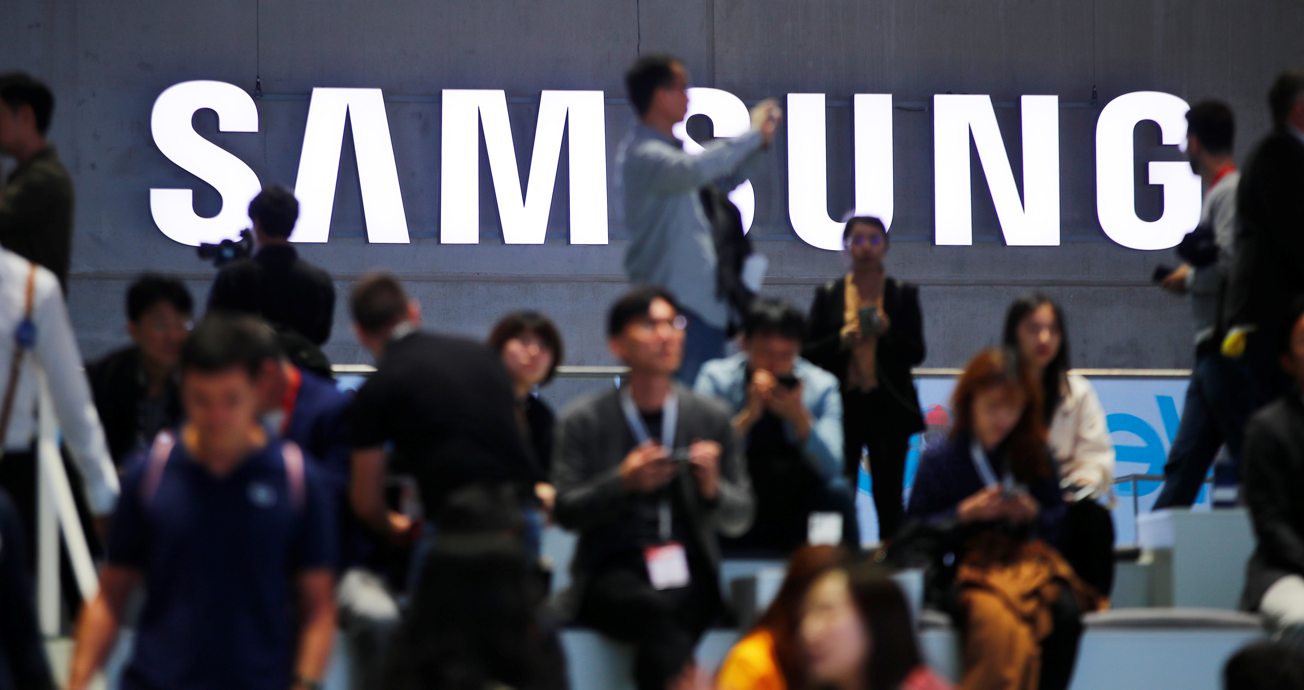 People sit in front of a Samsung logo at the IFA consumer tech fair in Berlin, Germany, September 6, 2019. REUTERS/Hannibal Hanschke