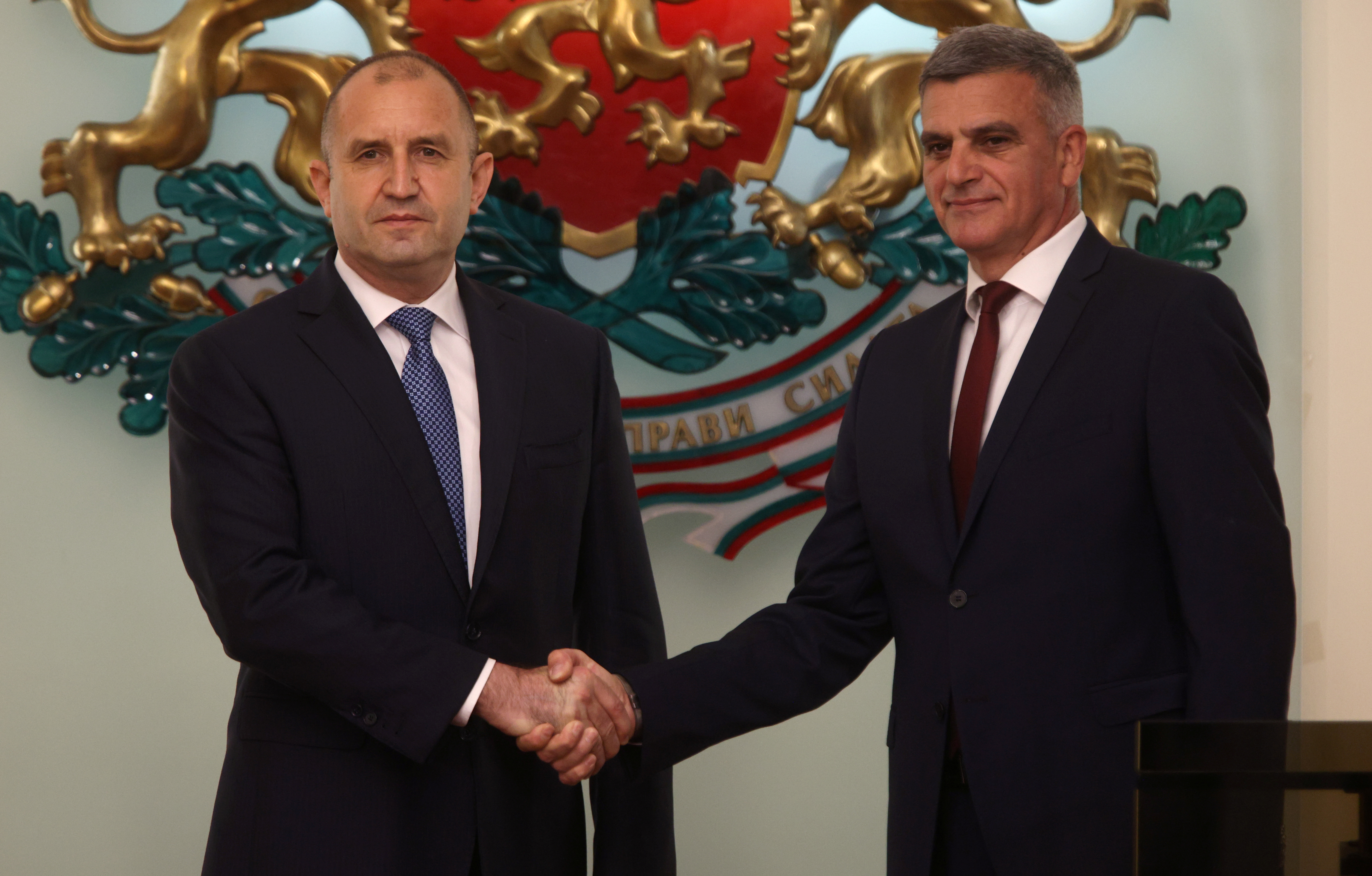 Newly appointed caretaker Prime Minister Stefan Yanev shakes hands with Bulgaria's President Rumen Radev during an official ceremony in Sofia, Bulgaria, May 12, 2021. REUTERS/Stoyan Nenov