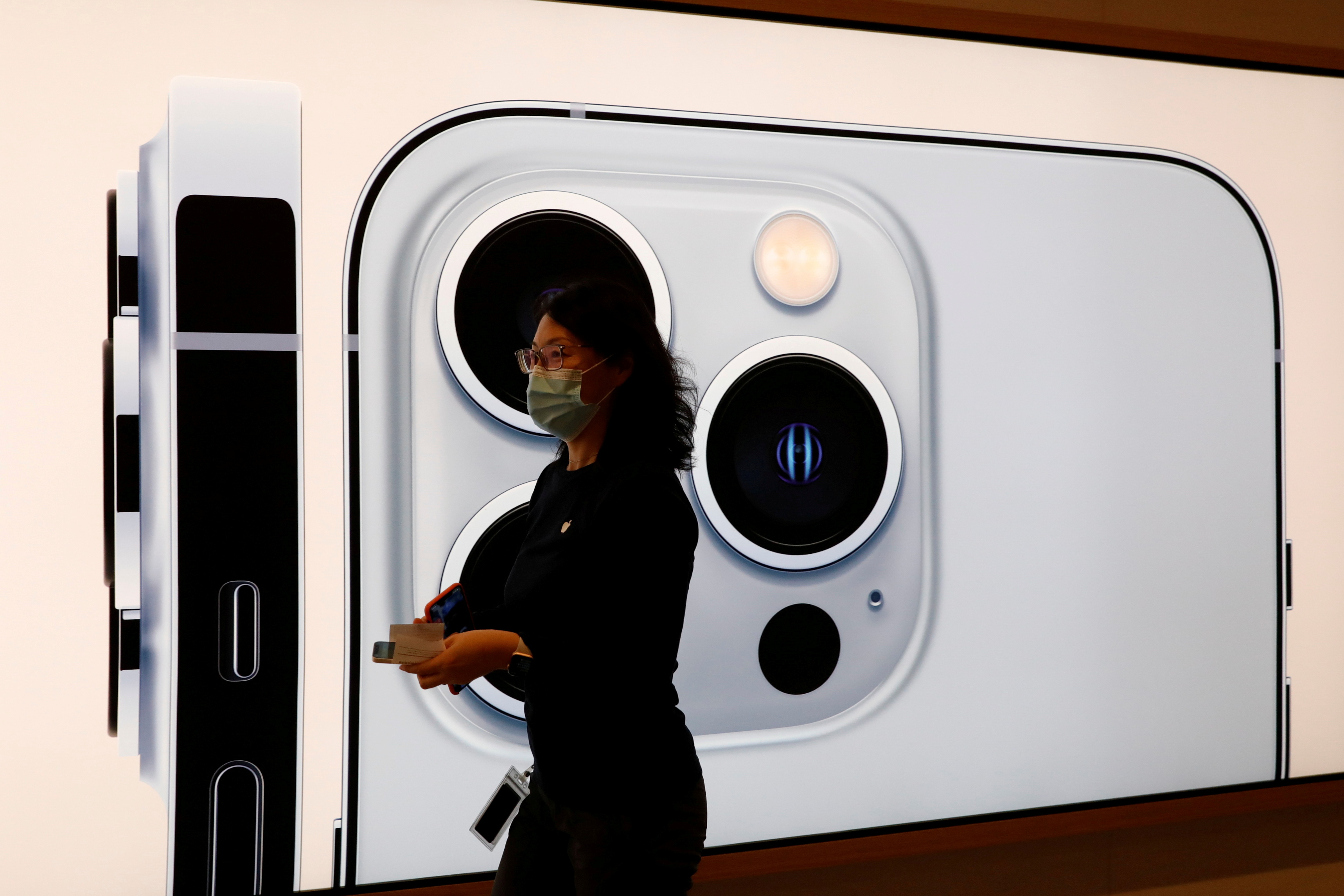 An Apple employee wearing a face mask walks past an image of an iPhone 13 Pro at an Apple Store on the day the new Apple iPhone 13 series goes on sale, in Beijing, China, September 24, 2021. REUTERS/Carlos Garcia Rawlins/File Photo