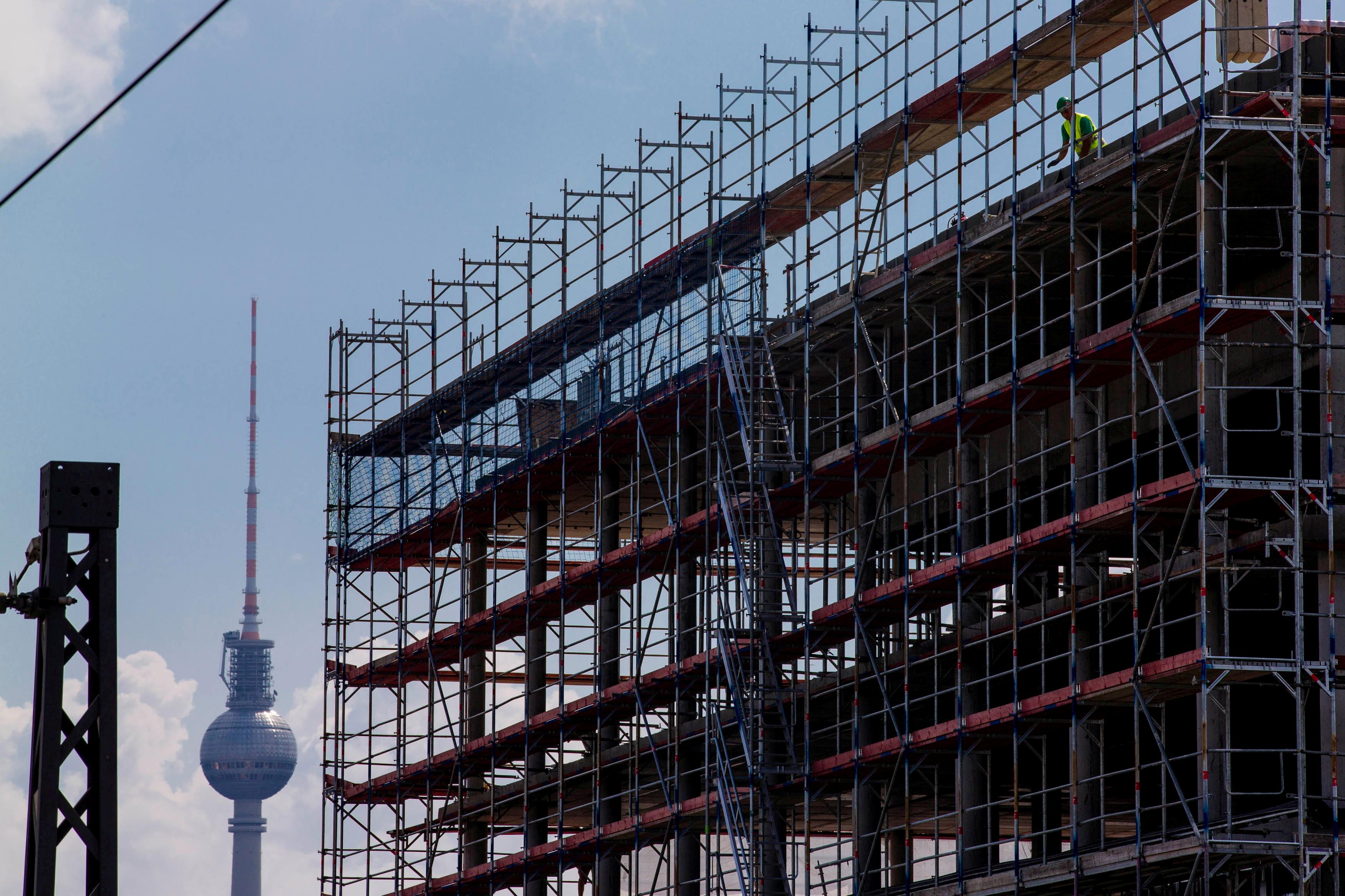 7年2014月XNUMX日,在柏林Fernsehturm电视塔附近的一个建筑工地上,在脚手架后面看到一名工人。路透社/托马斯·彼得/文件图片
