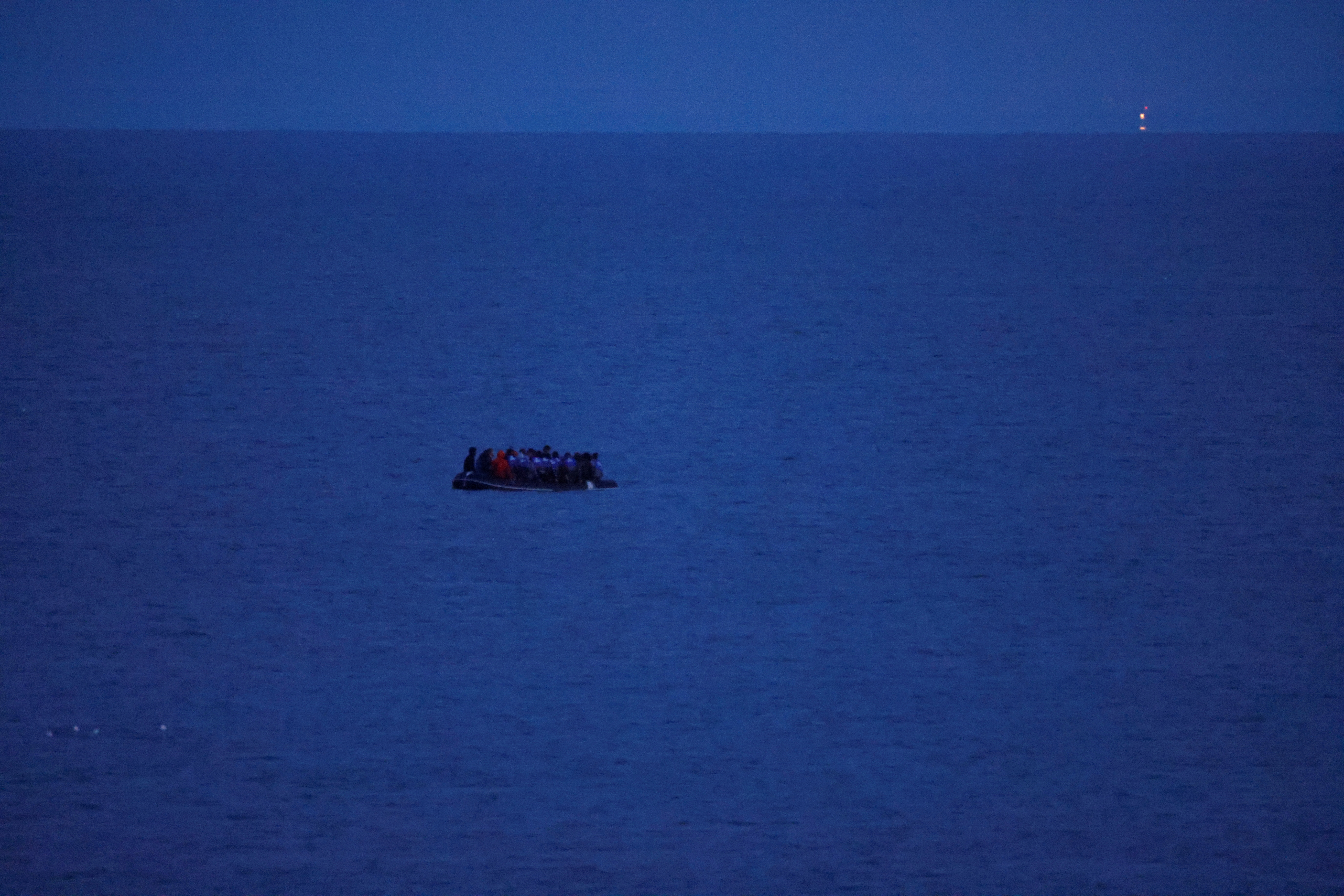 A dinghy with a group of migrants on board leaves the coast of northern France near Wimereux to reach Britain, September 13, 2021. REUTERS/Pascal Rossignol