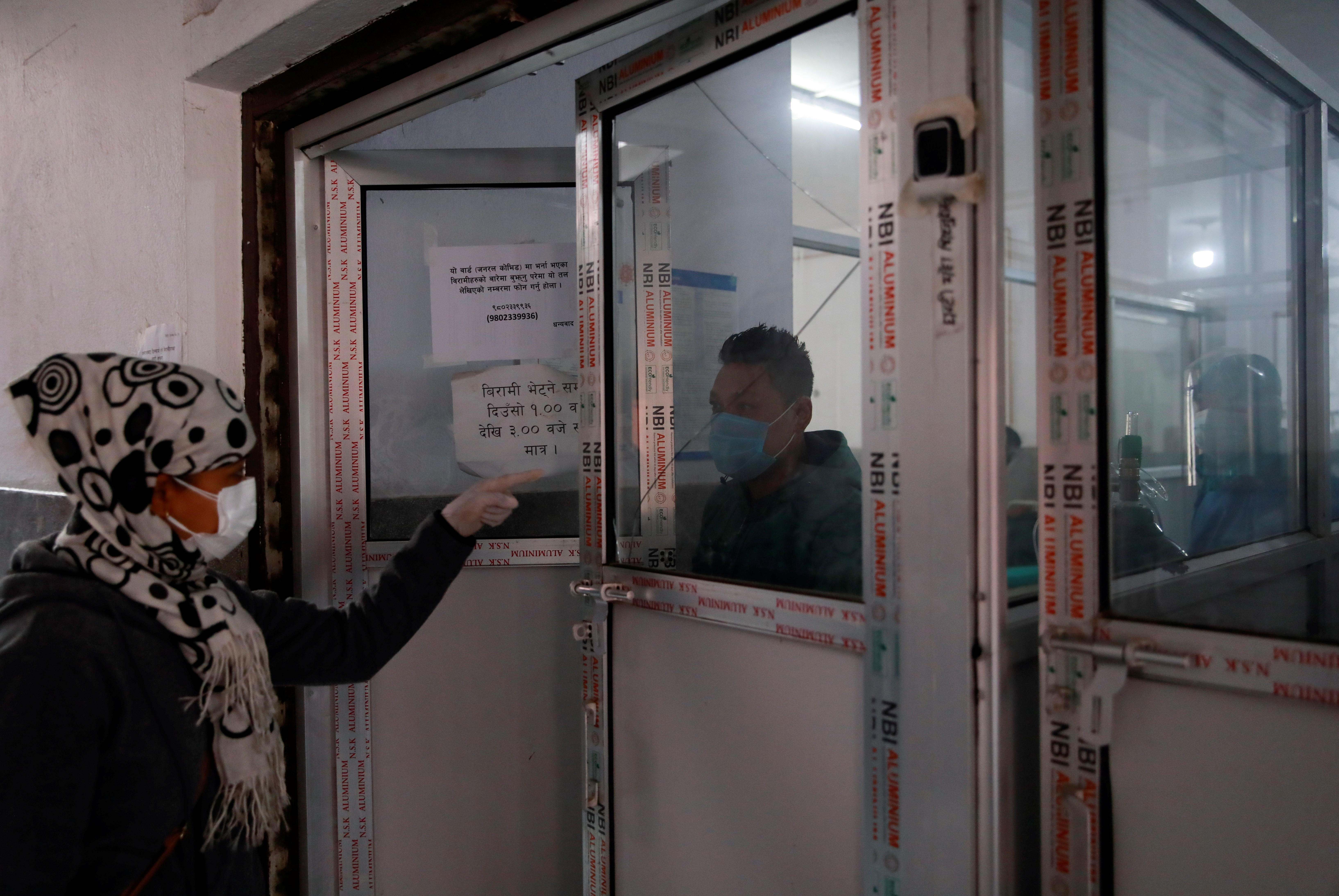 A visitor (L) speaks with a patient (C) at the entrance of COVID ward as the major second wave of the coronavirus disease (COVID-19) surges in Kathmandu, Nepal April 26, 2021. REUTERS/Navesh Chitrakar