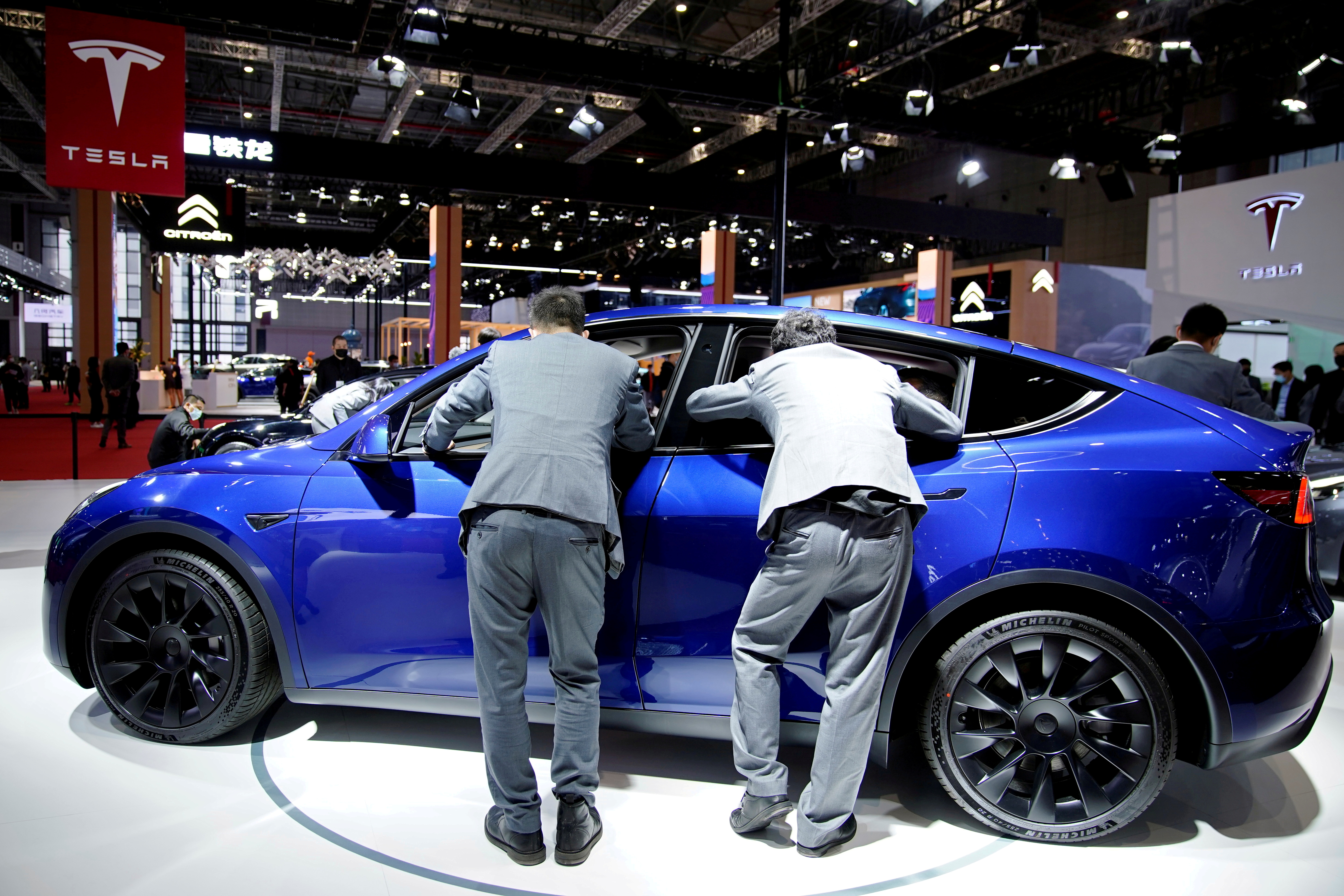 Visitors check an electric vehicle (EV) displayed at the Tesla booth during a media day for the Auto Shanghai show in Shanghai, China April 20, 2021. REUTERS/Aly Song/File Photo/File Photo