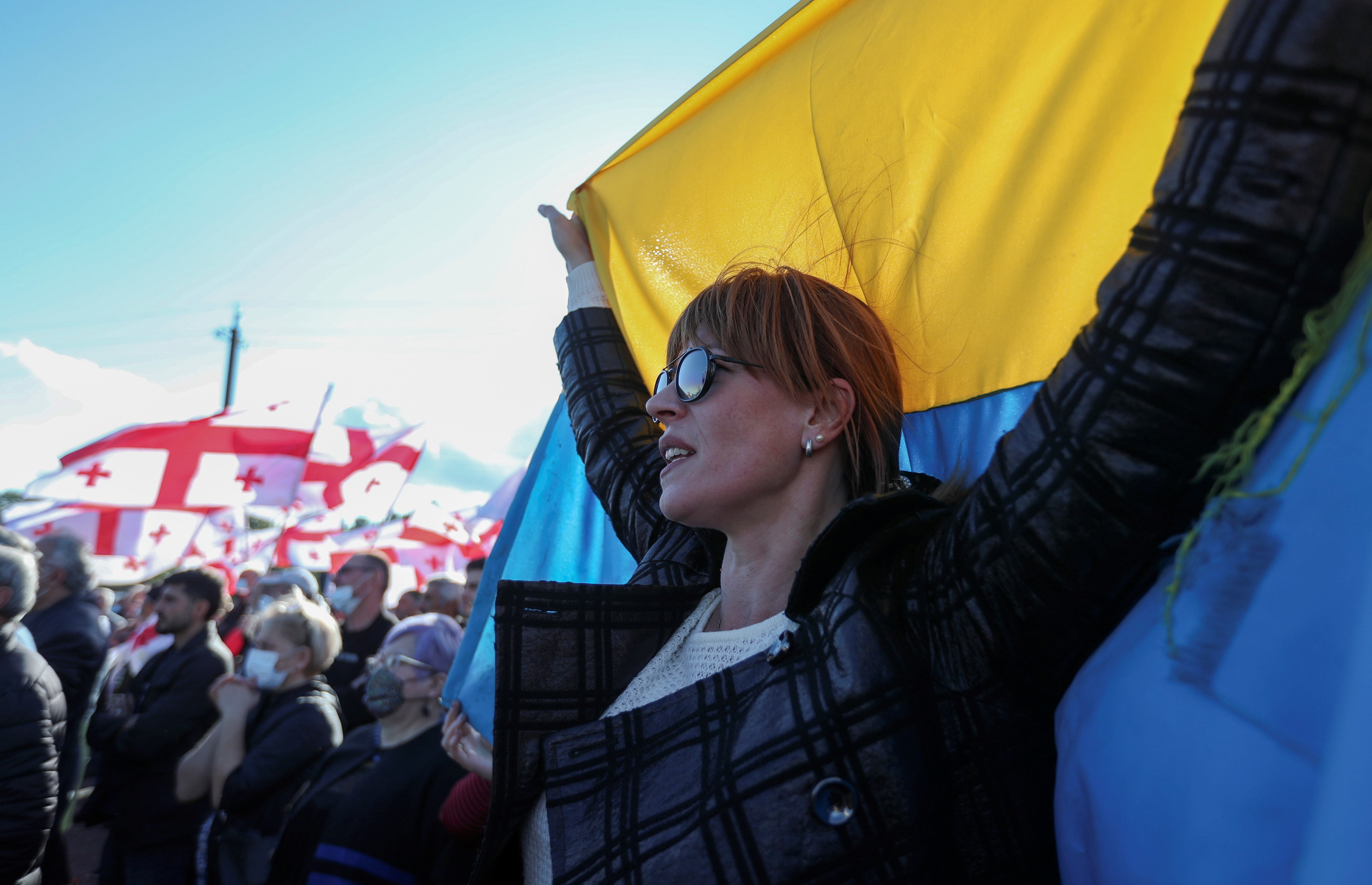 A participant holds a Ukrainian flag during a rally held by supporters of Georgian ex-president Mikheil Saakashvili, who called for post-election street protests and was arrested upon his arrival in Georgia despite facing imprisonment, near a jail in Rustavi, Georgia October 4, 2021. REUTERS/Irakli Gedenidze