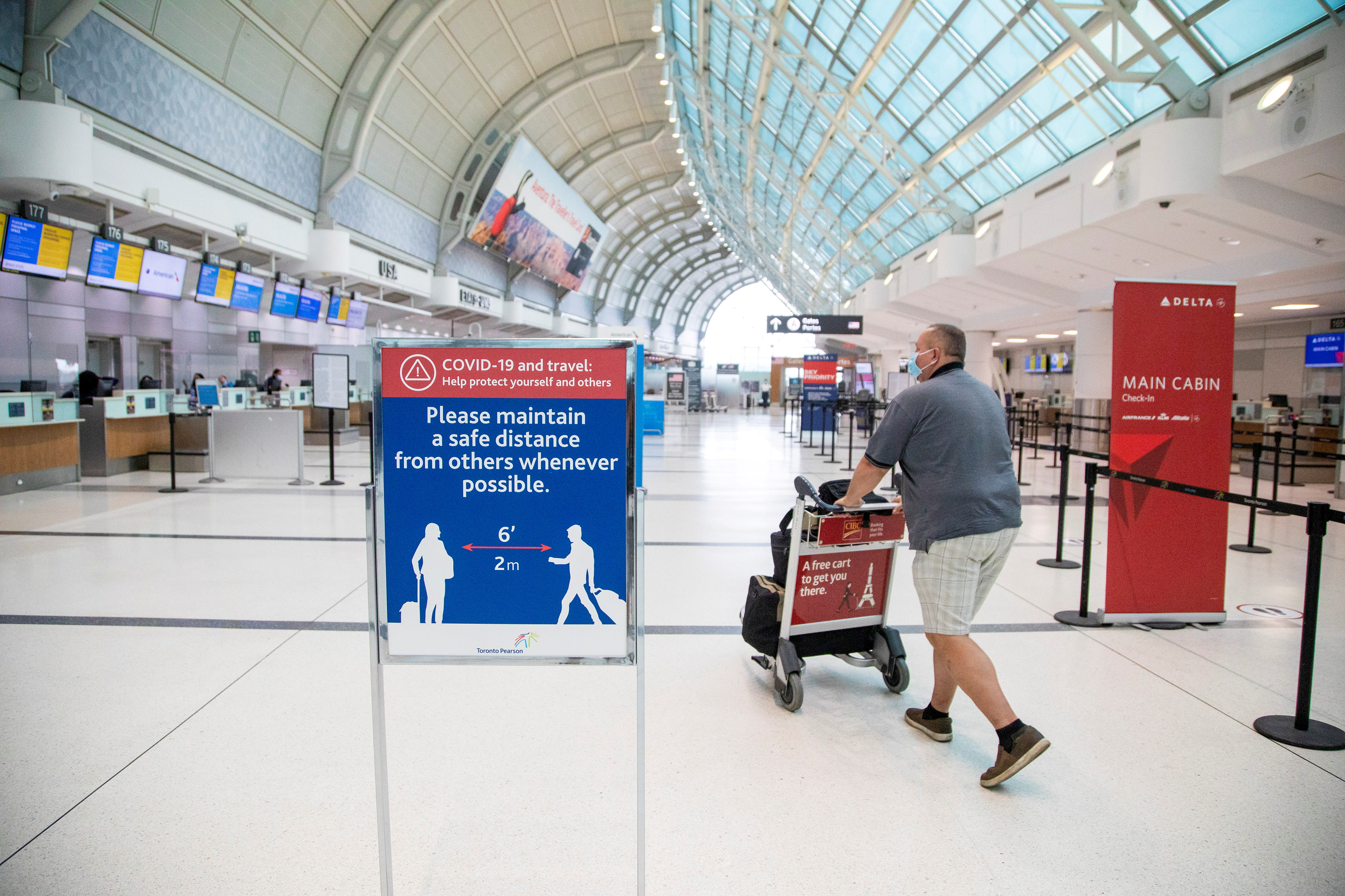 A man pushes a baggage cart wearing a mandatory face mask as a