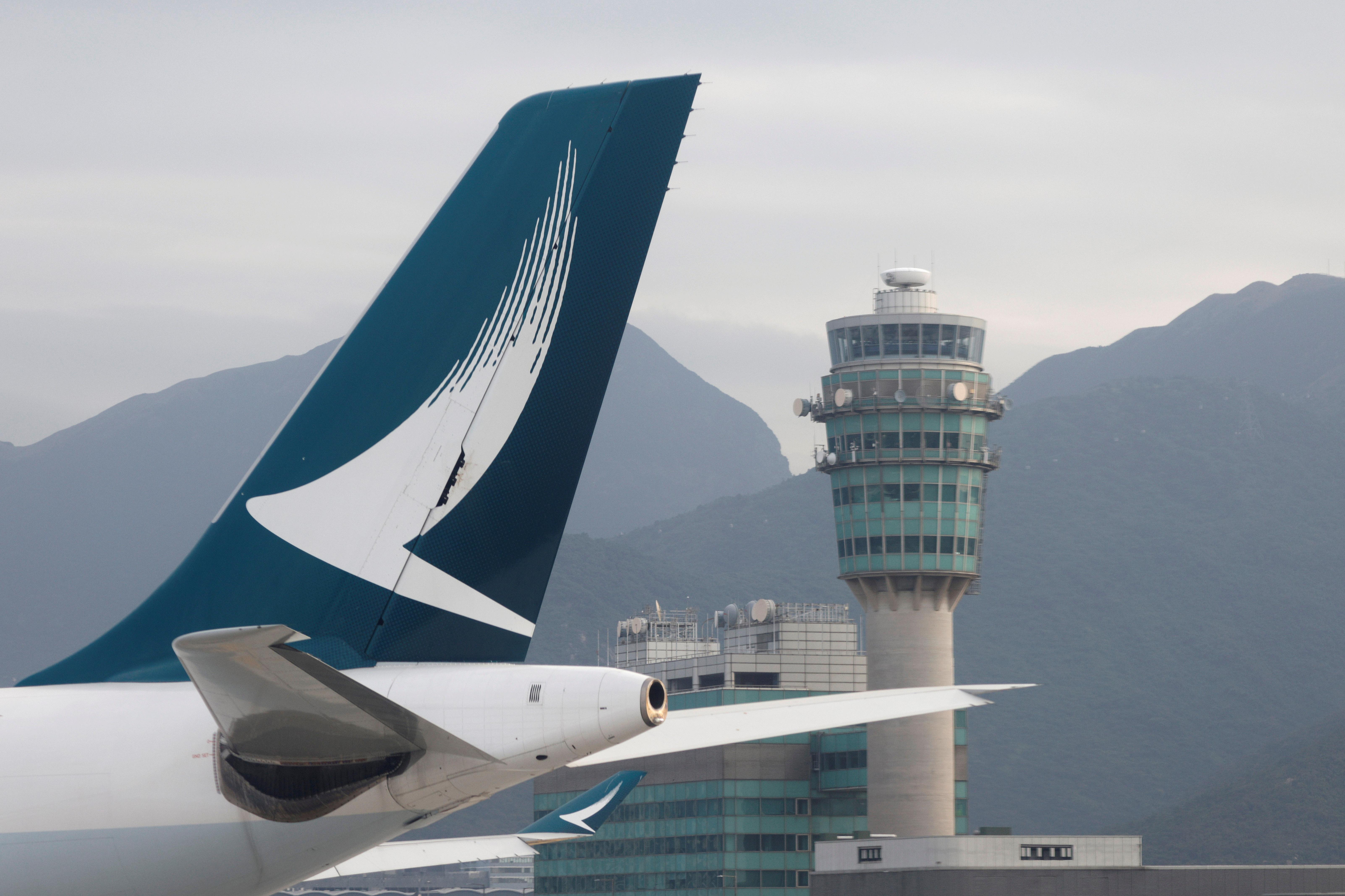 A Cathay Pacific aircraft is seen in front of an air traffic control tower at the Hong Kong International Airport, Hong Kong, China October 24 2020. REUTERS/Tyrone Siu/File Photo