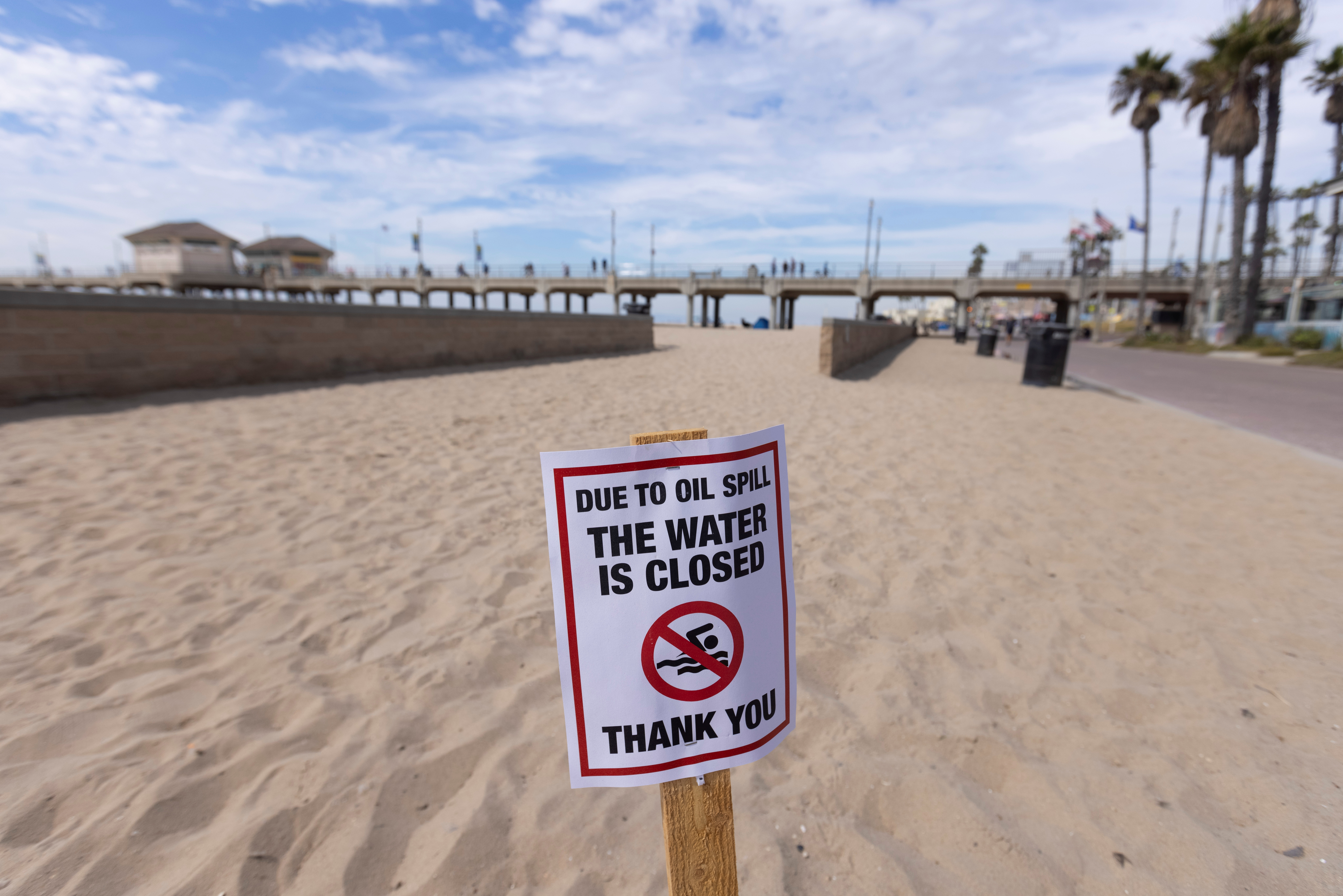 A warning sign is posted for people to stay out of the water after a major oil spill off the coast of California came ashore in Huntington Beach, California, U.S.,  October 4, 2021. REUTERS/Mike Blake