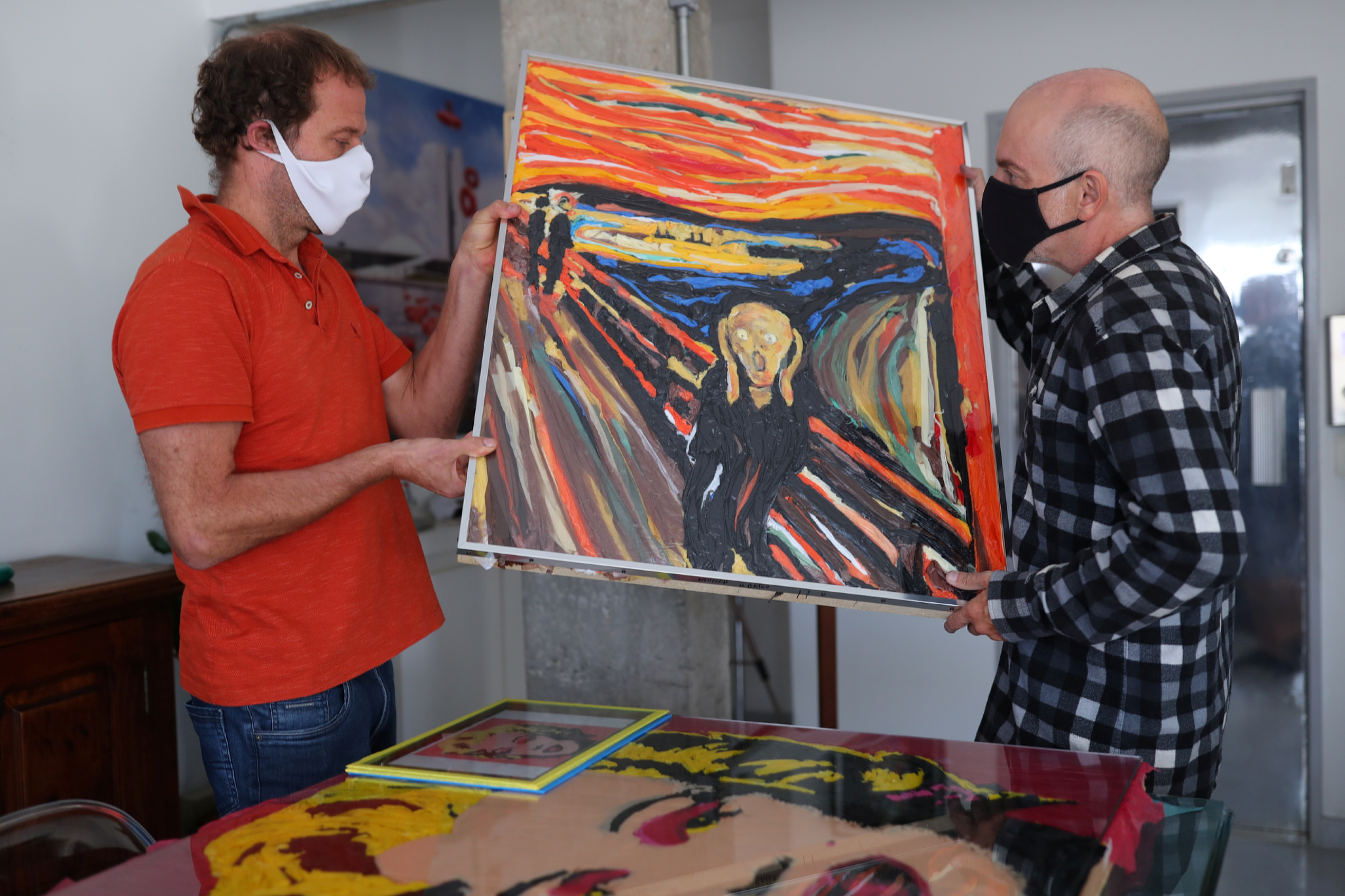 Brazilian artist Eduardo Srur and his assistant Rogerio Canella hold the recreation of the painting 'The Scream' by Edvard Munch made with plastic as part of his new series 'Plastic Nature' in his studio in Sao Paulo, Brazil May 27, 2021. Picture taken May 27, 2021.  REUTERS/Amanda Perobelli