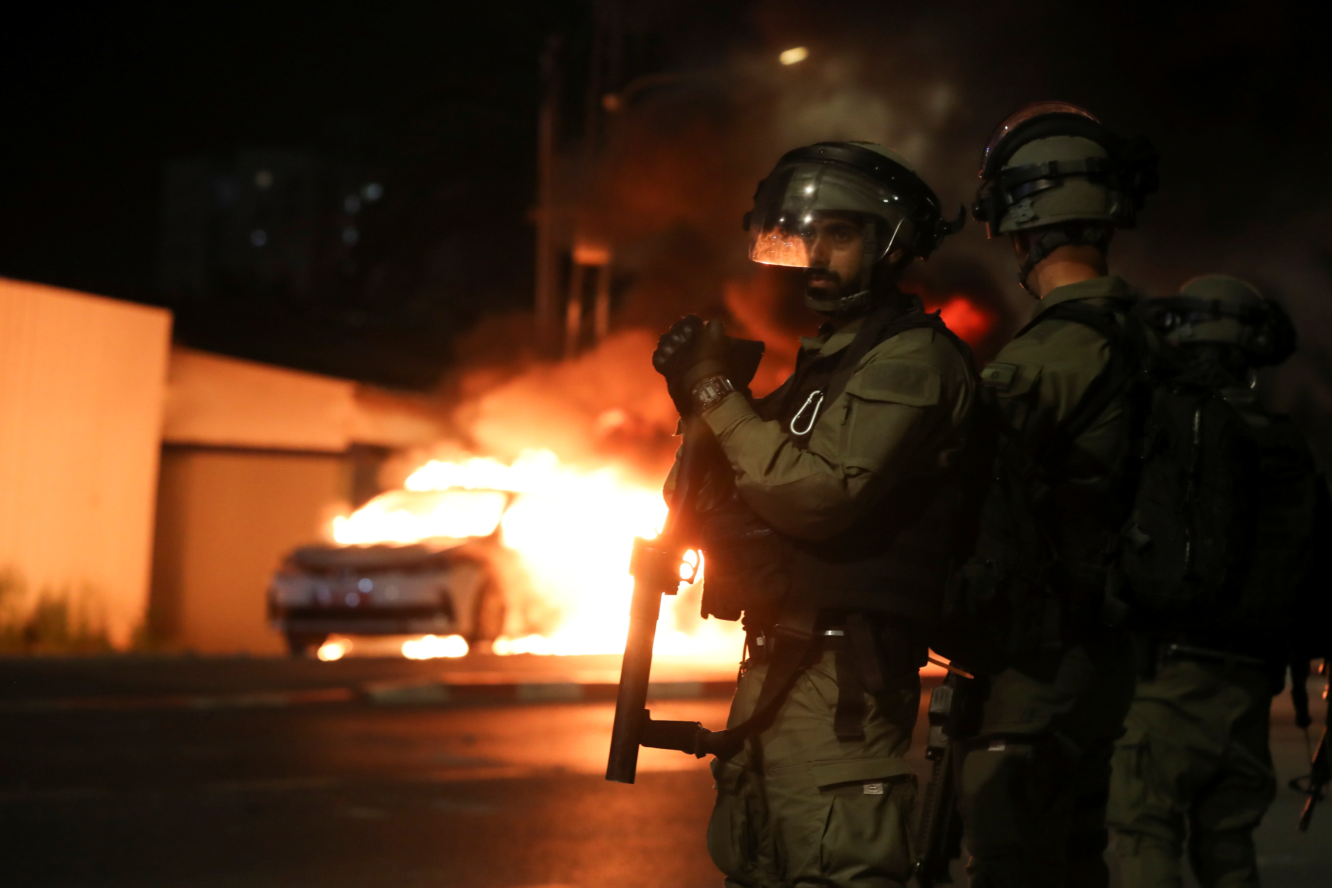 Israeli security force members stand near a burning Israeli police car during clashes between Israeli police and members of the country's Arab minority in the Arab-Jewish town of Lod, Israel May 12, 2021. REUTERS/Ammar Awad