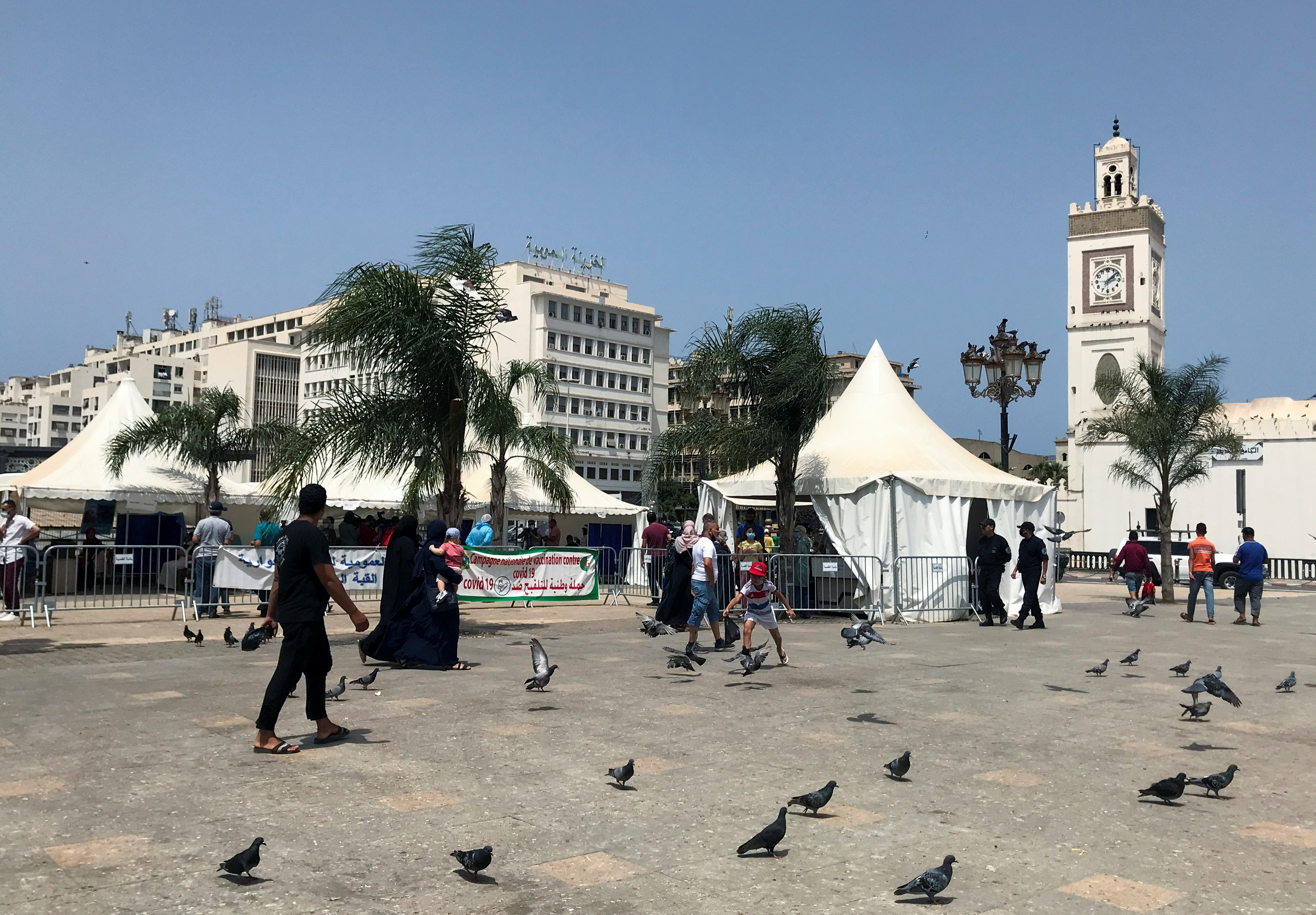 People walk past tents erected during a coronavirus disease (COVID-19) vaccination campaign that is taking place outside mosques, after Friday Prayers in Algiers, Algeria July 9, 2021. REUTERS/Abdelaziz Boumzar