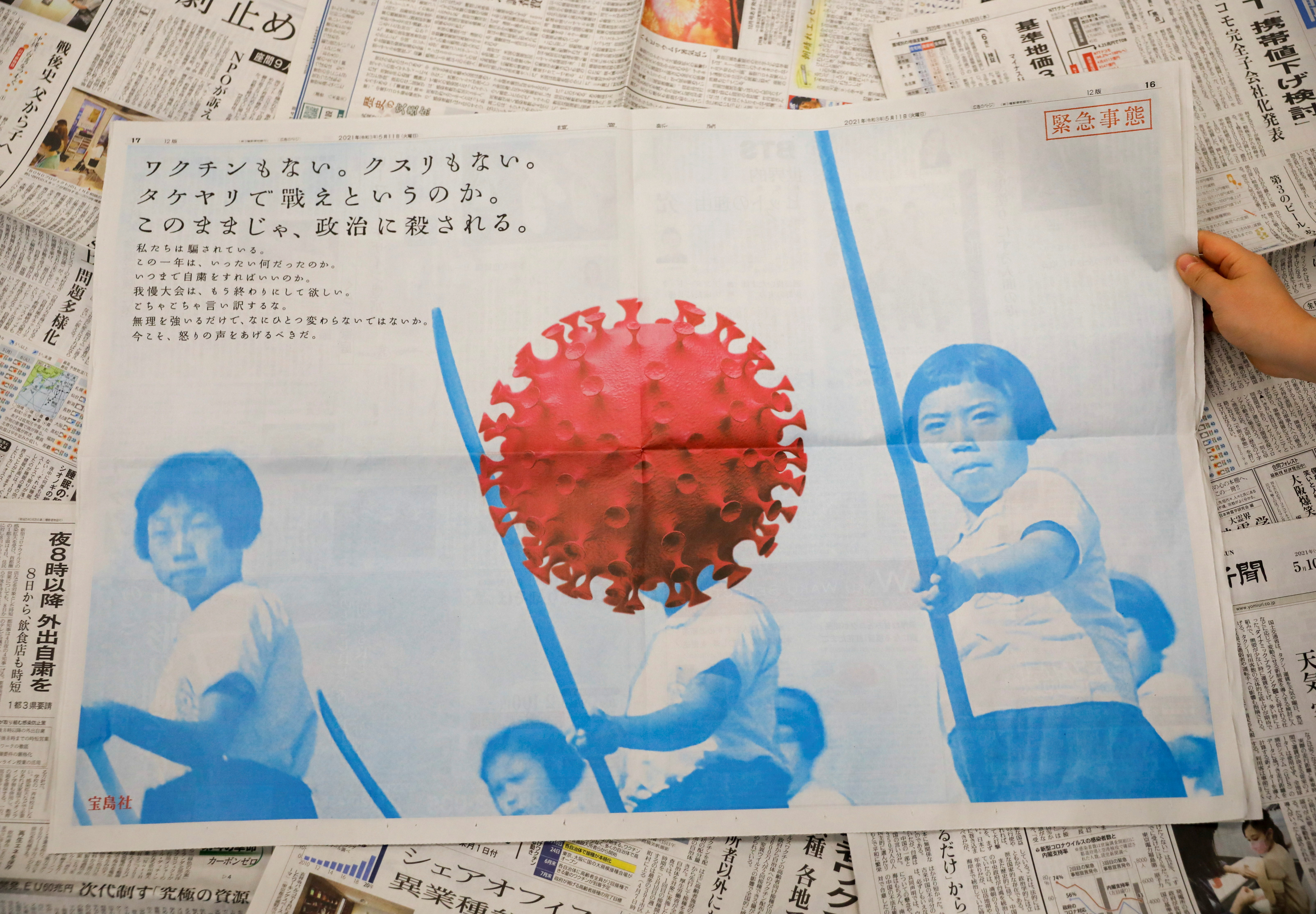 A full-page ad by magazine publisher Takarajimasha, with message reading 'No vaccine, no medication. Are we supposed to fight with bamboo spears? If things continue as they are, politics are going to kill us,' is seen on a newspaper in Tokyo, Japan May 11, 2021.  REUTERS/Issei Kato