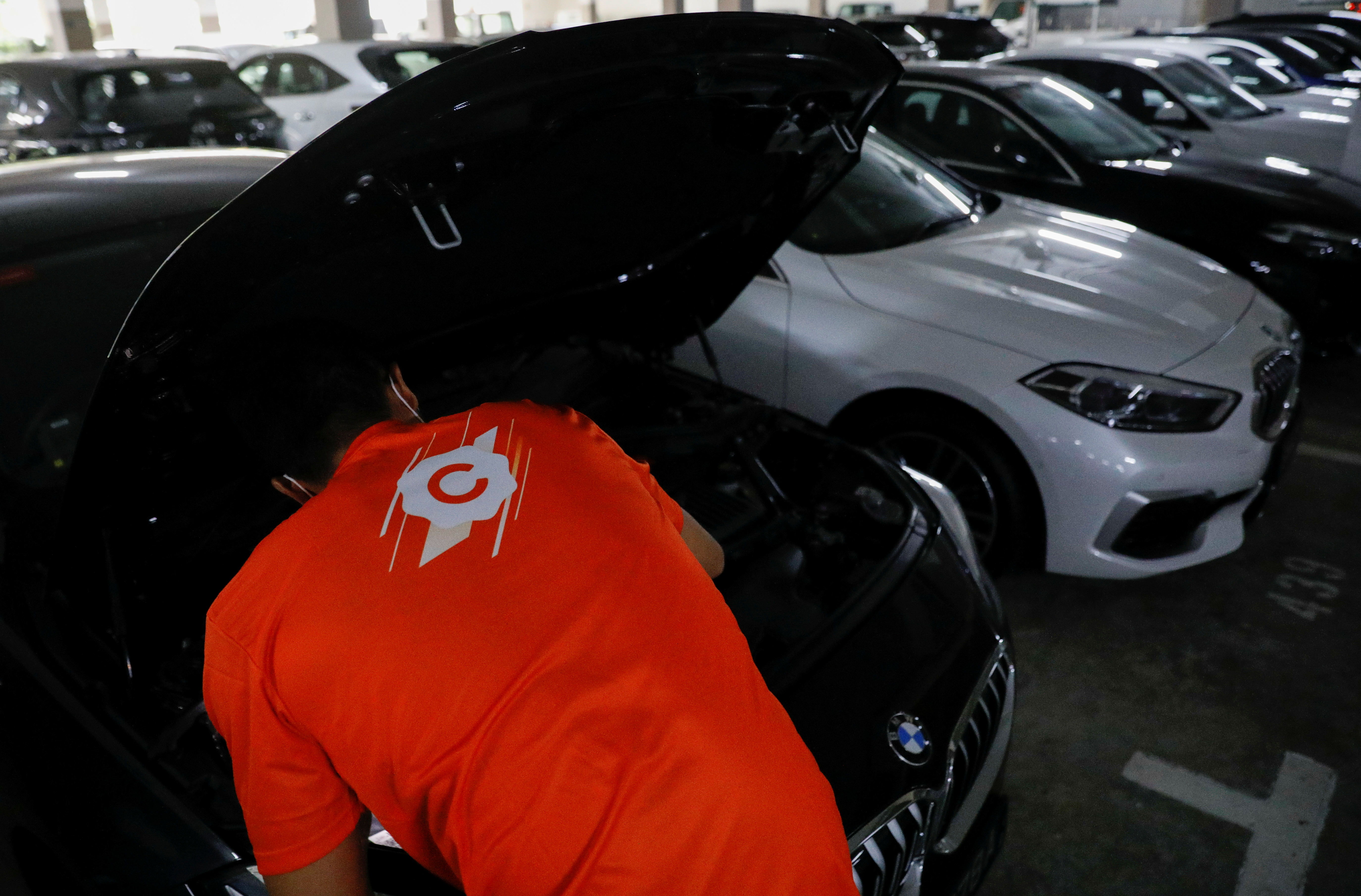 Goh Keane, assistant general manager of Carro, checks on one of their cars at their showroom in Singapore June 15, 2021.   REUTERS/Edgar Su