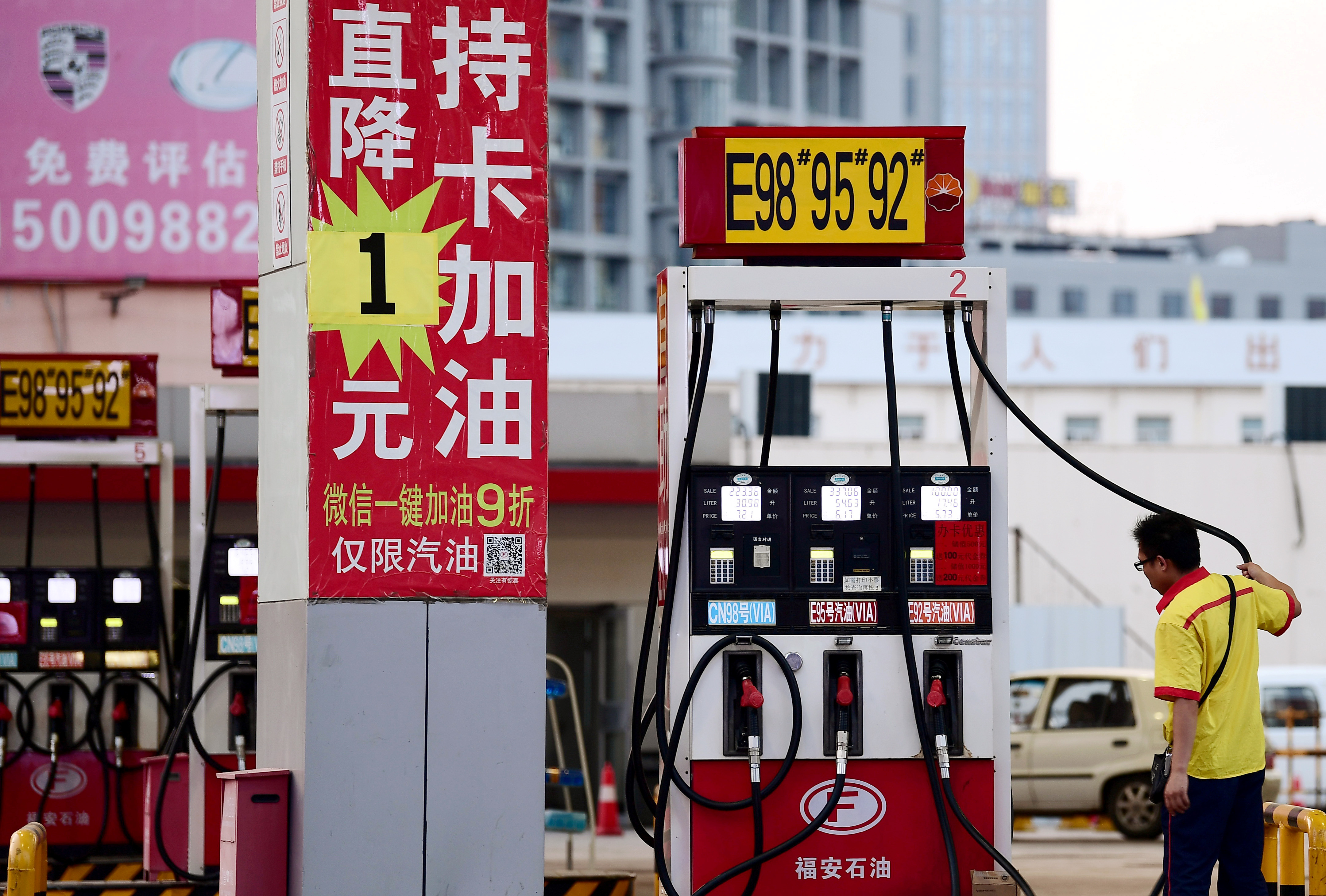 A pump attendant is seen next to a discount advertisement for gasolines at a Petrochina petrol station in Shenyang, Liaoning province, China June 24, 2019.  REUTERS/Stringer