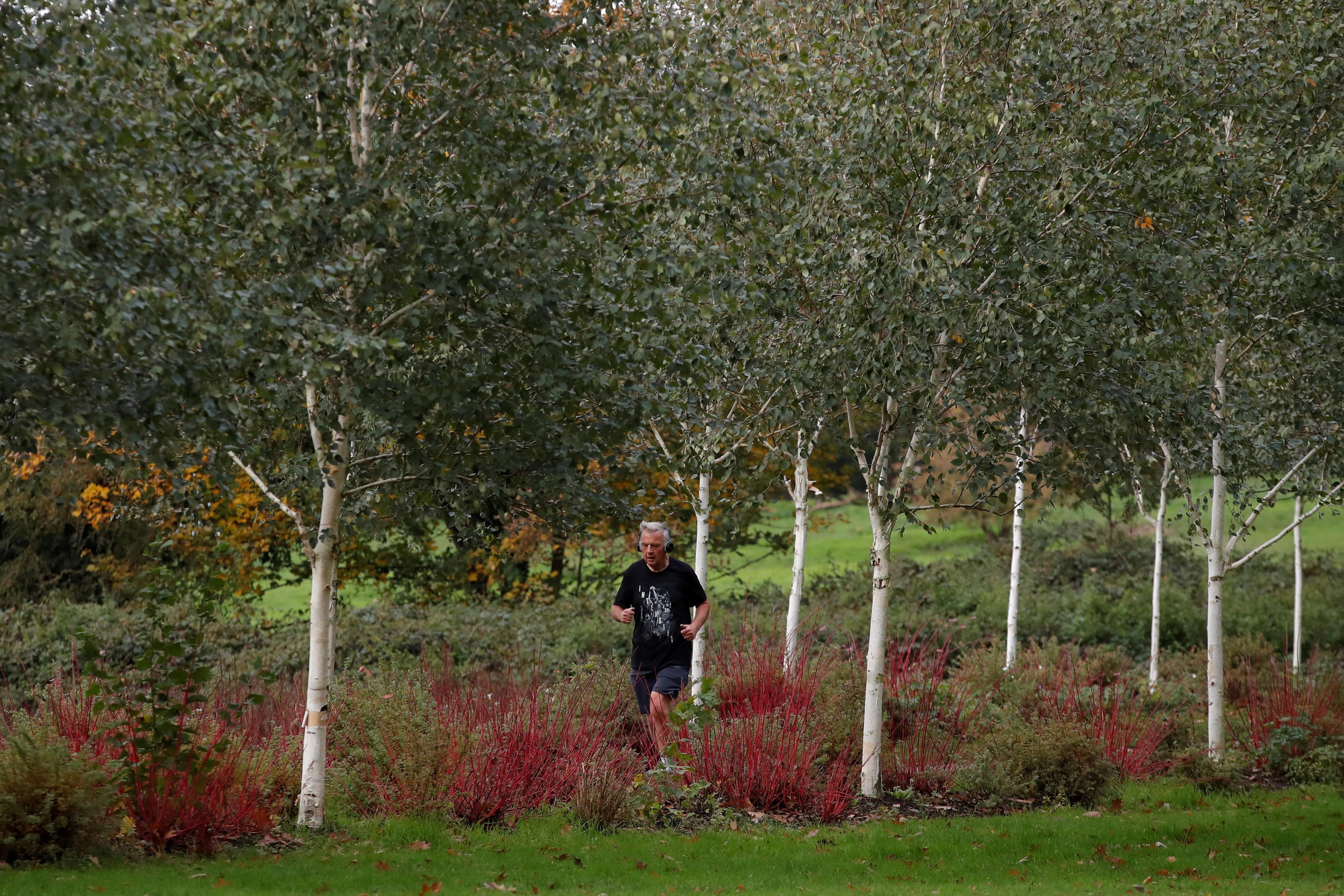 A man runs through trees in Barclay Park, Hoddesdon, Britain October 22, 2020. REUTERS/Andrew Couldridge/File Photo