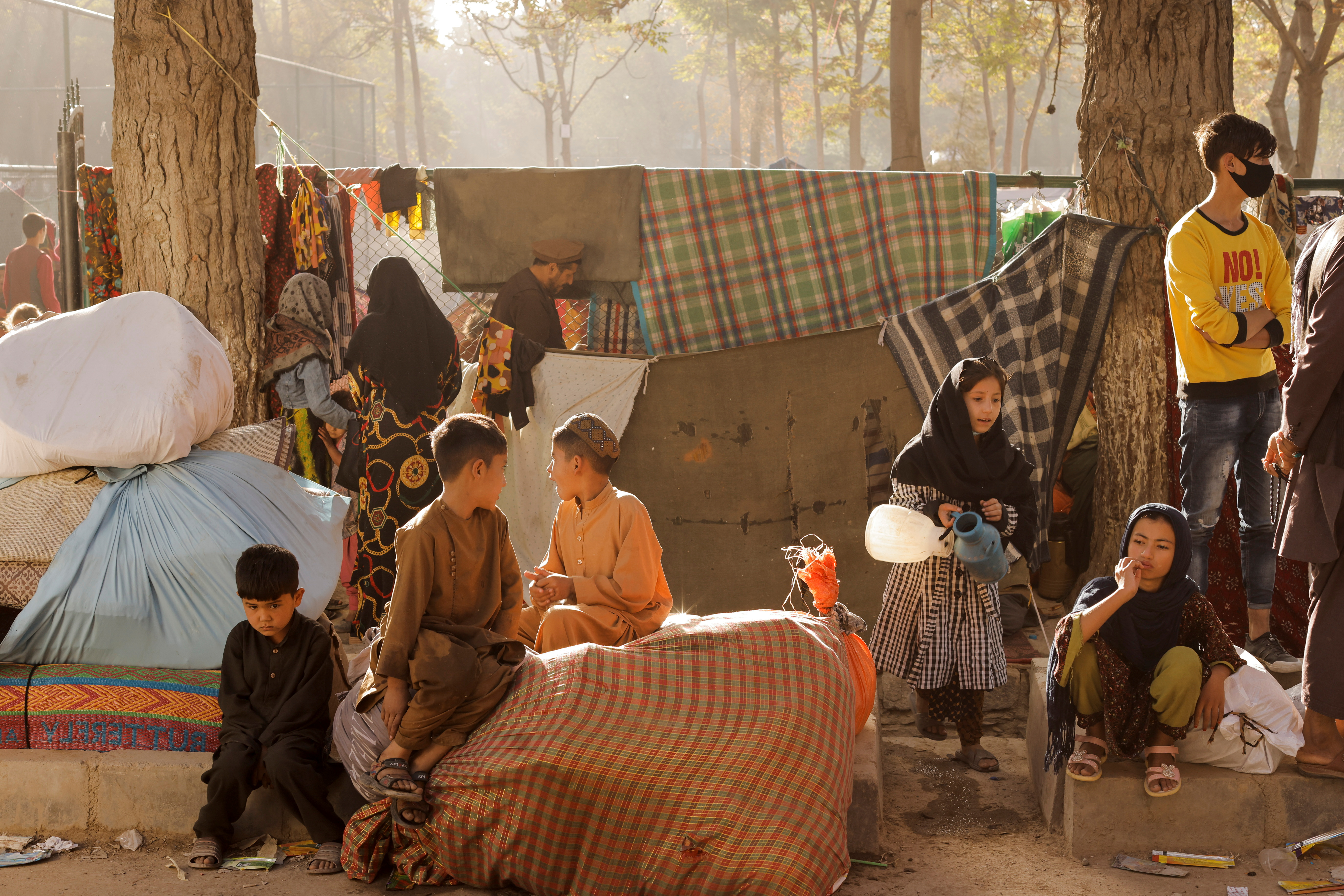 Afghan families, who are among displaced people fleeing the violence in their provinces, sit with their belongings as they prepare to return to their provinces, at a makeshift shelter at Shahr-e Naw park, in Kabul, Afghanistan October 4, 2021. REUTERS/Jorge Silva