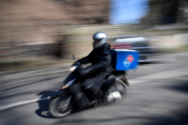 A Domino's pizza delivery person drives a scooter in a residential street, as the spread of the coronavirus disease (COVID-19) continues, in west London, Britain, March 24, 2020. REUTERS/Toby Melville