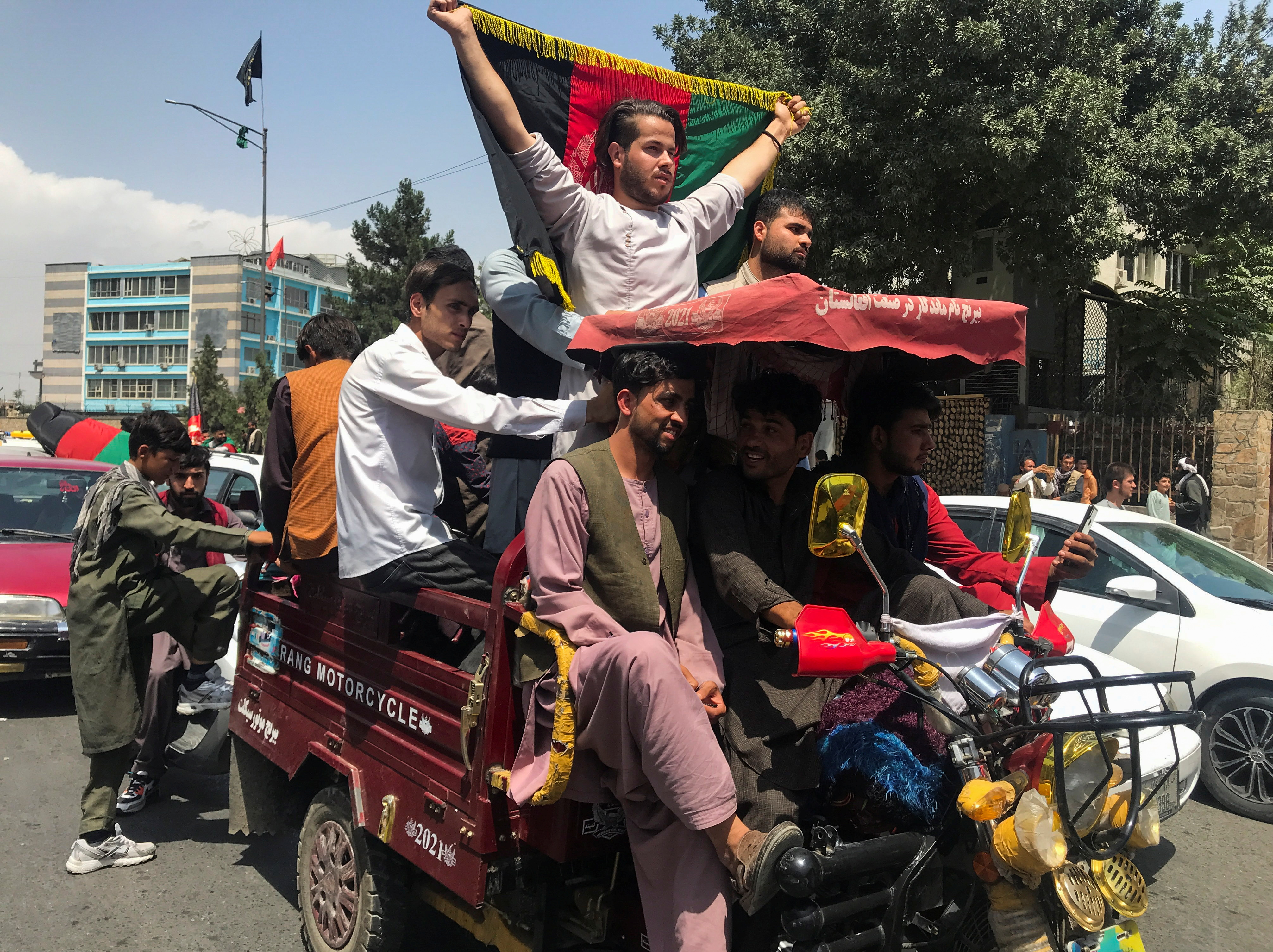 People carry the national flag at a protest held during the Afghan Independence Day in Kabul, Afghanistan August 19, 2021. REUTERS/Stringer