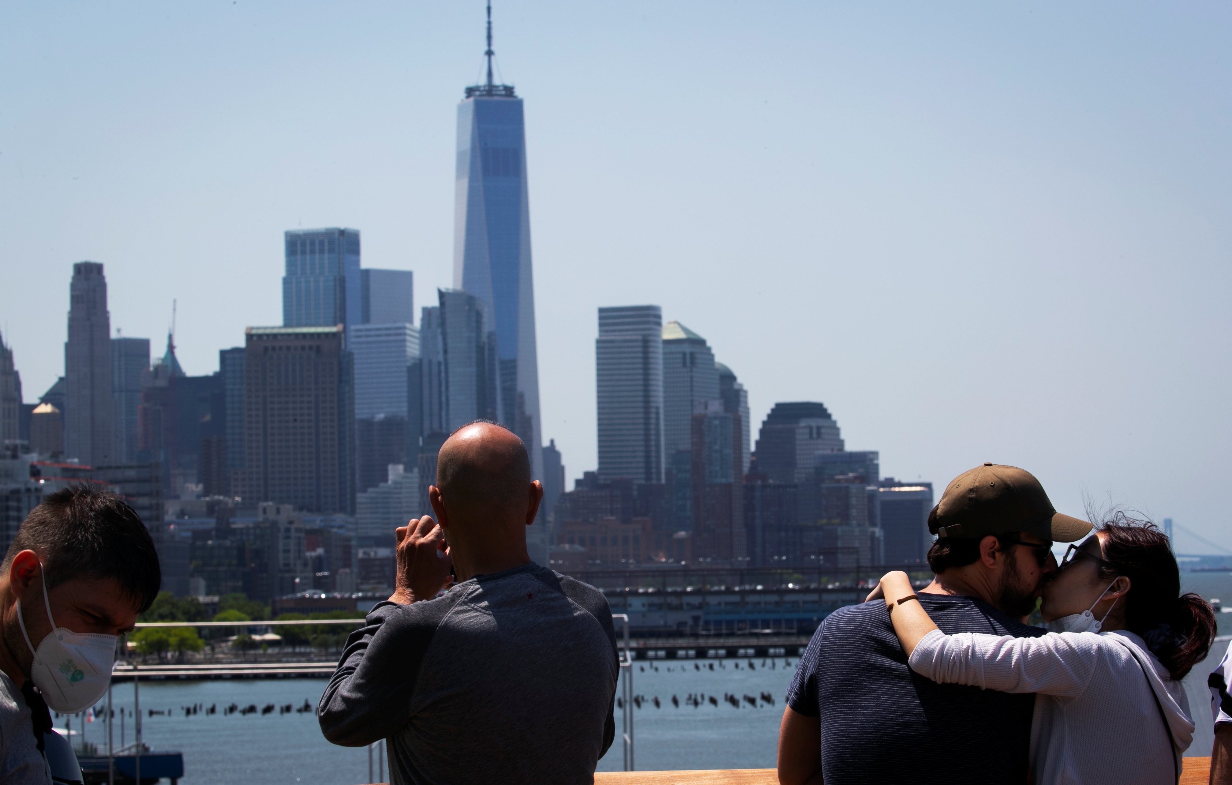 The skyline of lower Manhattan and the One World Trade Center tower are seen as people visit the peak of Little Island Park, almost three acres of new public park space which sits on stilts over the Hudson River and the remnants of Pier 54 in the larger Hudson River Park, on Manhattan's West Side, during the park's opening day in New York City, New York, U.S., May 21, 2021. REUTERS/Mike Segar