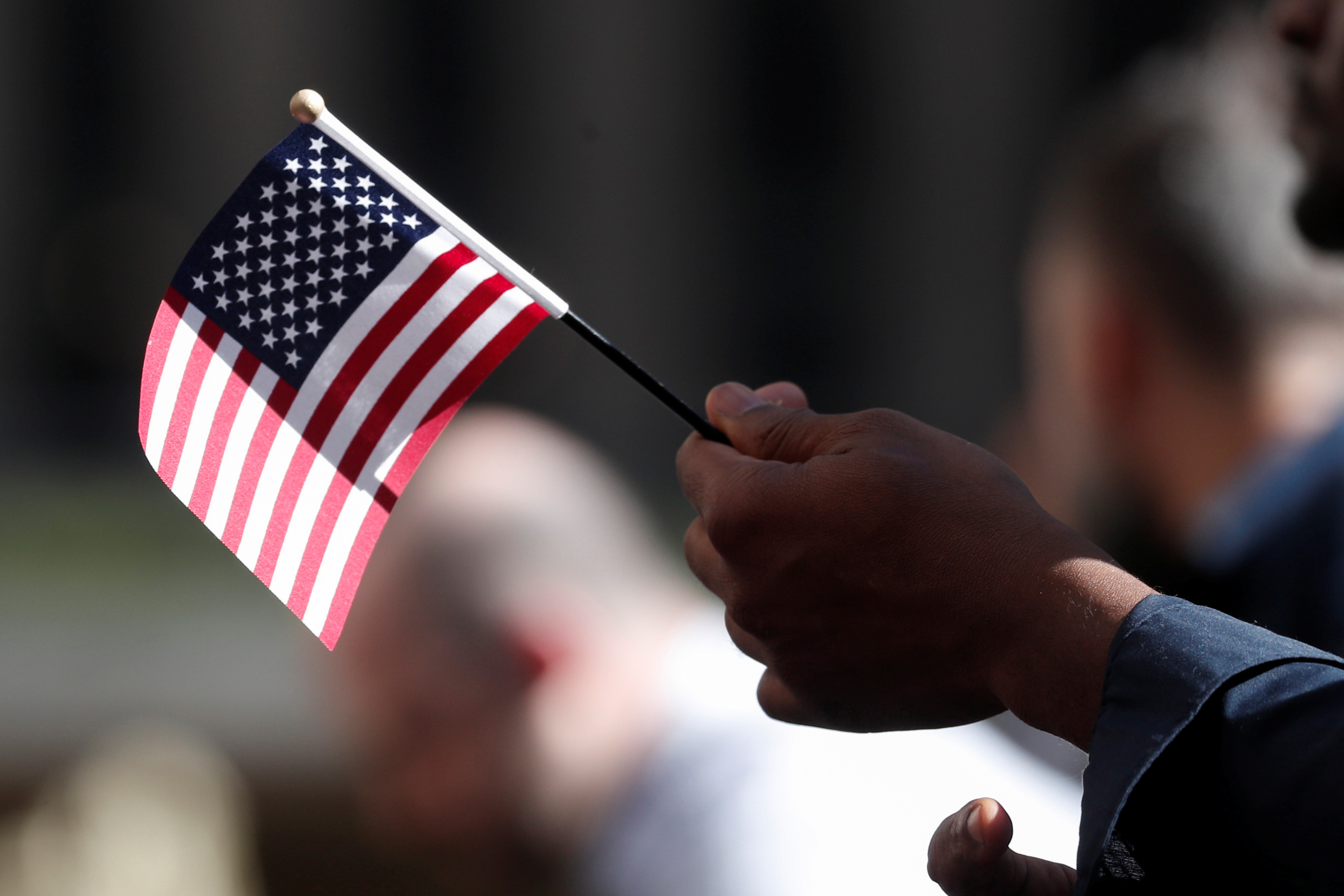 A citizenship candidate holds a flag during the U.S. Citizenship and Immigration Services (USCIS) naturalization ceremony at Rockefeller Plaza in New York City, U.S., September 17, 2019. REUTERS/Shannon Stapleton