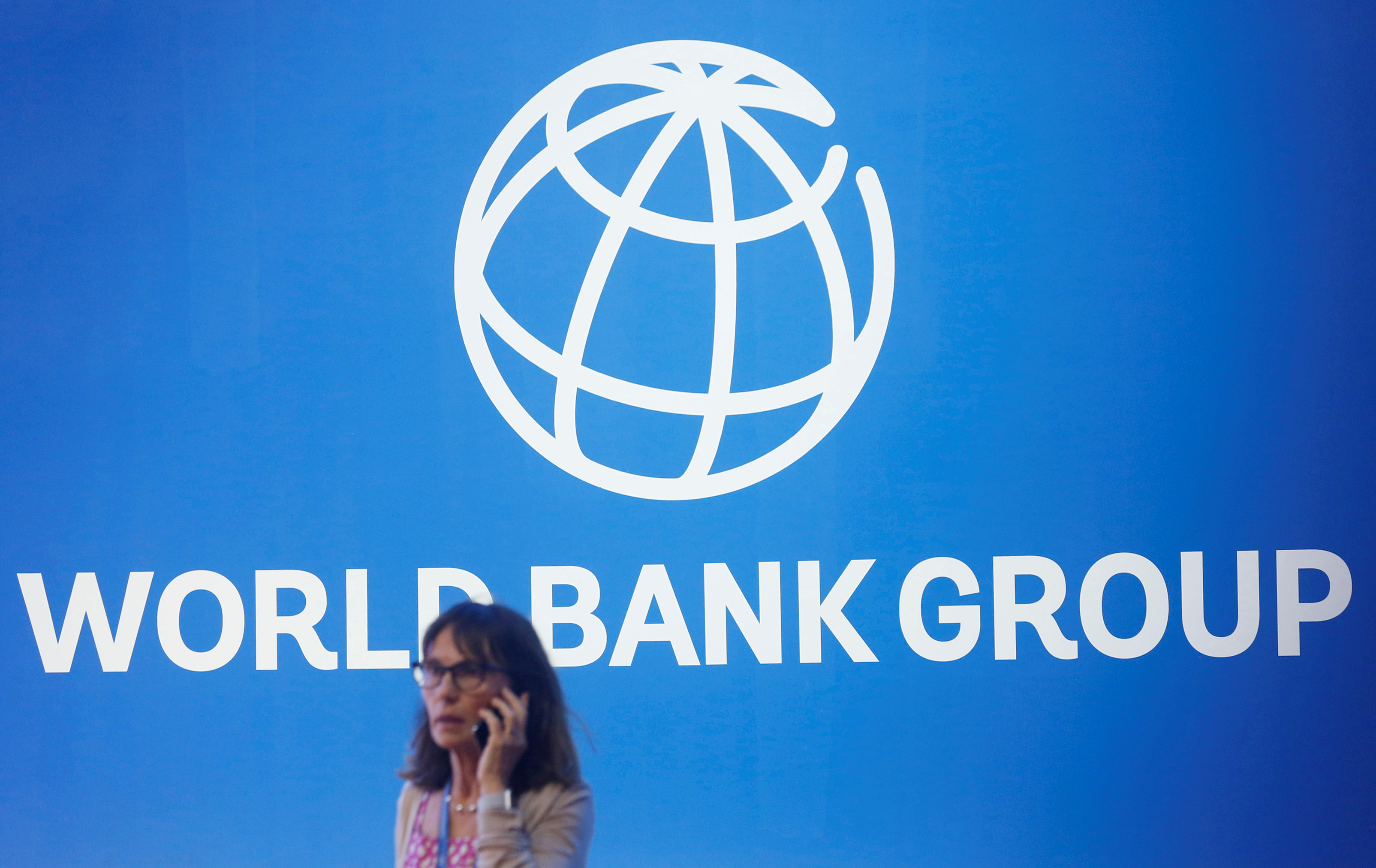 A participant stands near a logo of World Bank at the International Monetary Fund - World Bank Annual Meeting 2018 in Nusa Dua, Bali, Indonesia, October 12, 2018. REUTERS/Johannes P. Christo/File Photo