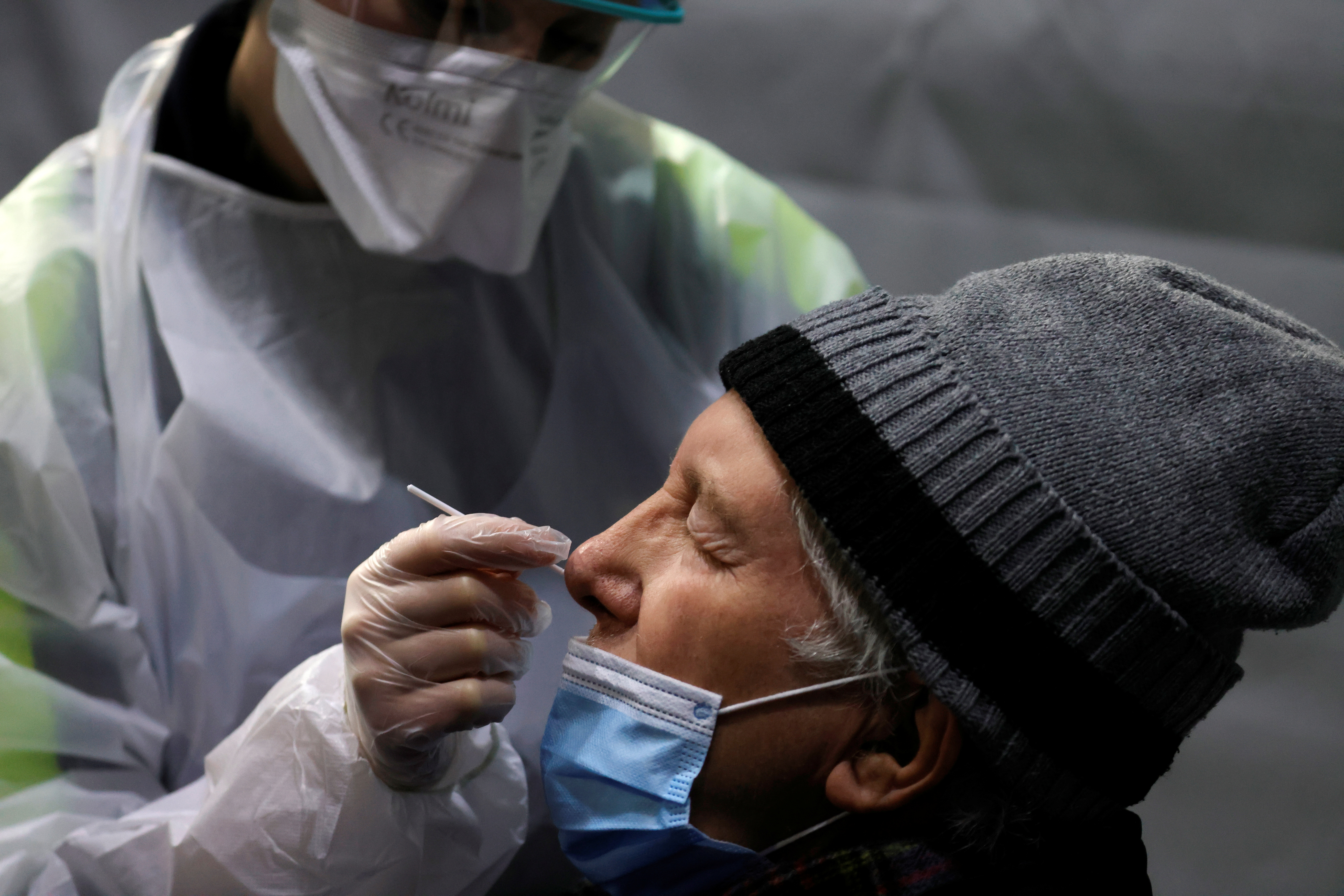 A medical worker administers a nasal swab to a patient at a coronavirus disease (COVID-19) testing center installed inside in the Kursaal concert hall in Dunkirk, France, February 18, 2021. REUTERS/Pascal Rossignol/File Photo