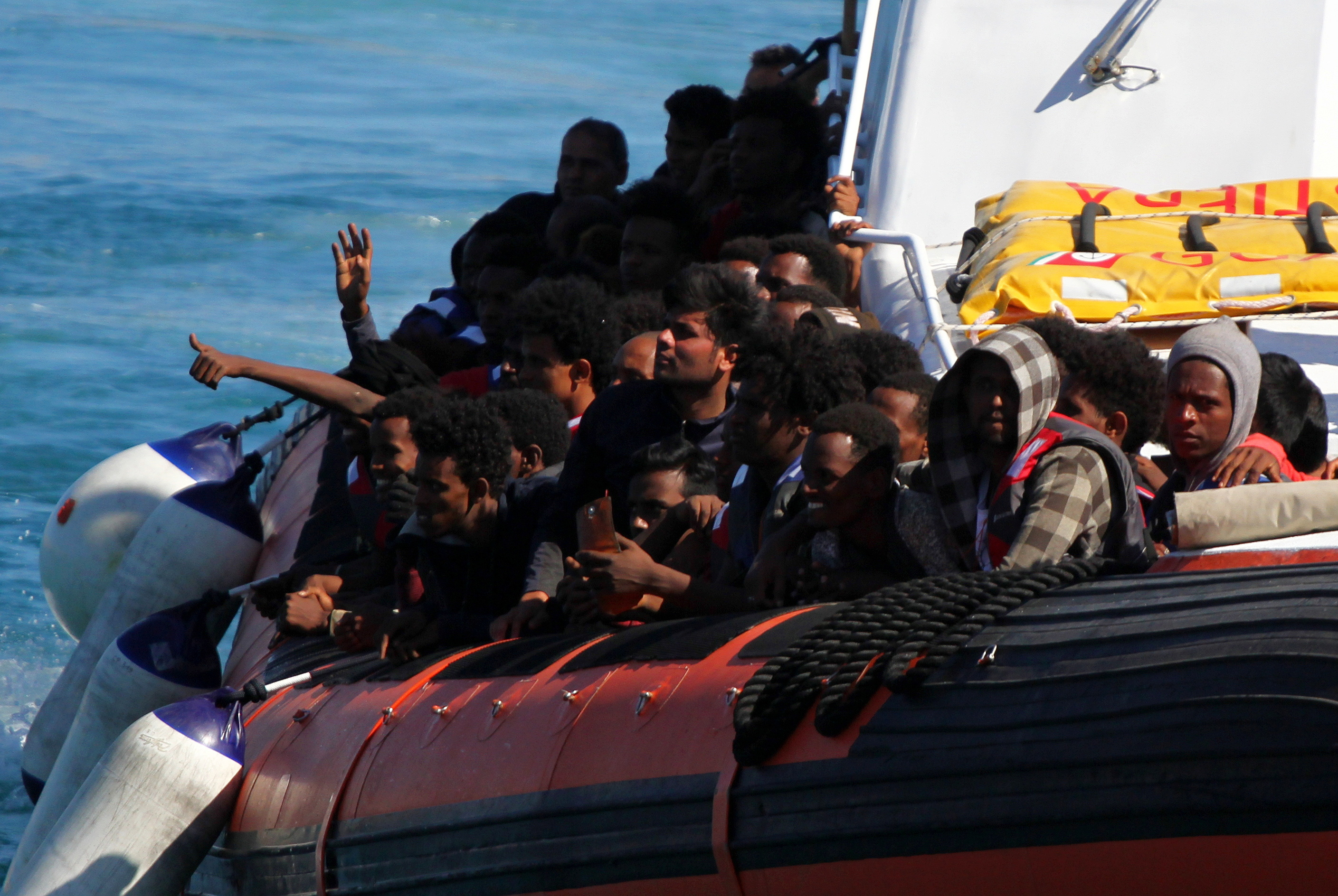 Migrants gesture as they approach aboard a coast guard vessel, part of the hundreds that arrived packed on boats, on the southern island of Lampedusa, Italy May 9, 2021. REUTERS/Mauro Buccarello