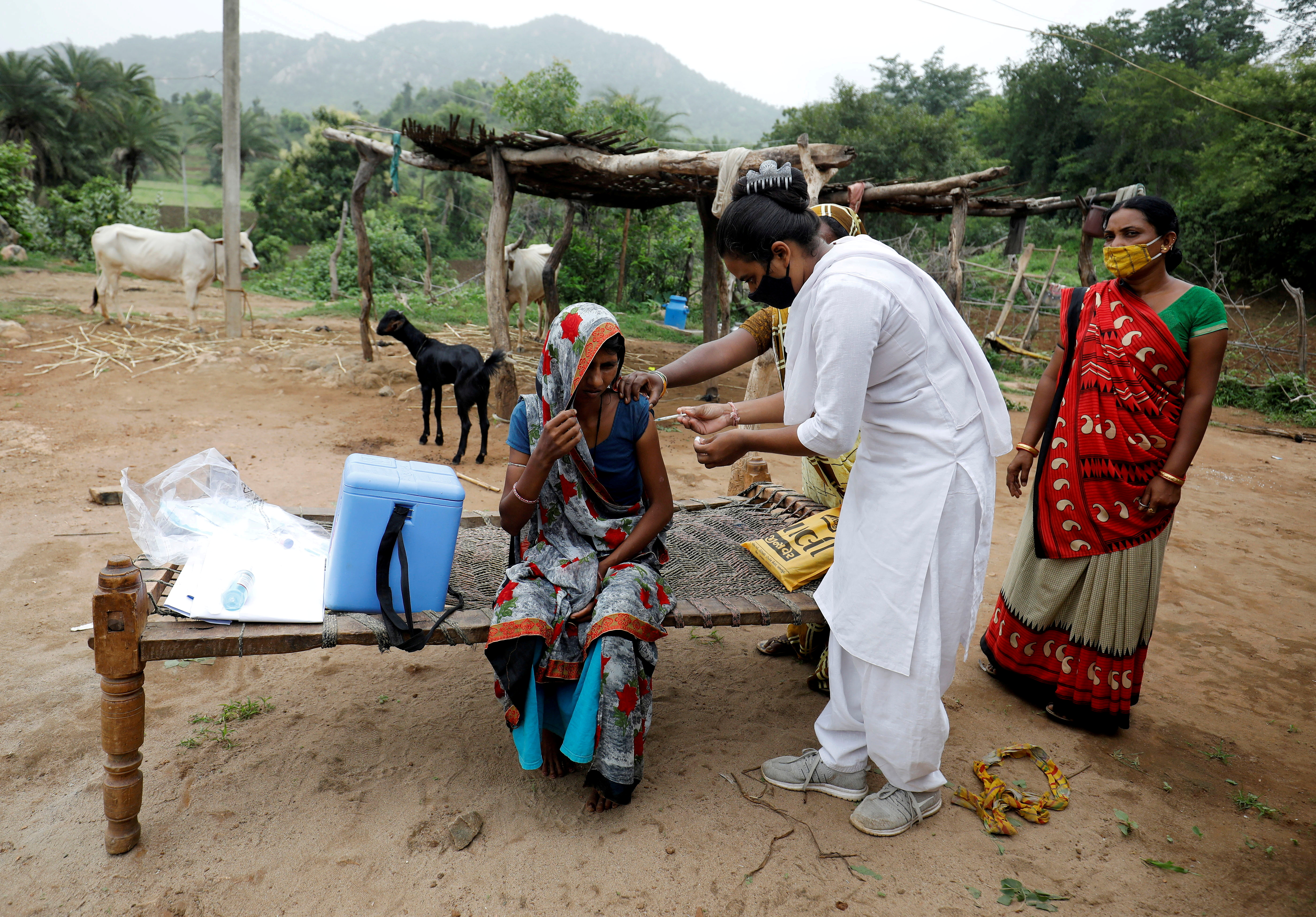 Healthcare worker Jankhana Prajapati gives a dose of the domestically manufactured COVISHIELD vaccine to villager Amiyaben Dabhi during a door-to-door vaccination drive in Banaskantha district in the western state of Gujarat, India, July 23, 2021. REUTERS/Amit Dave/File Photo