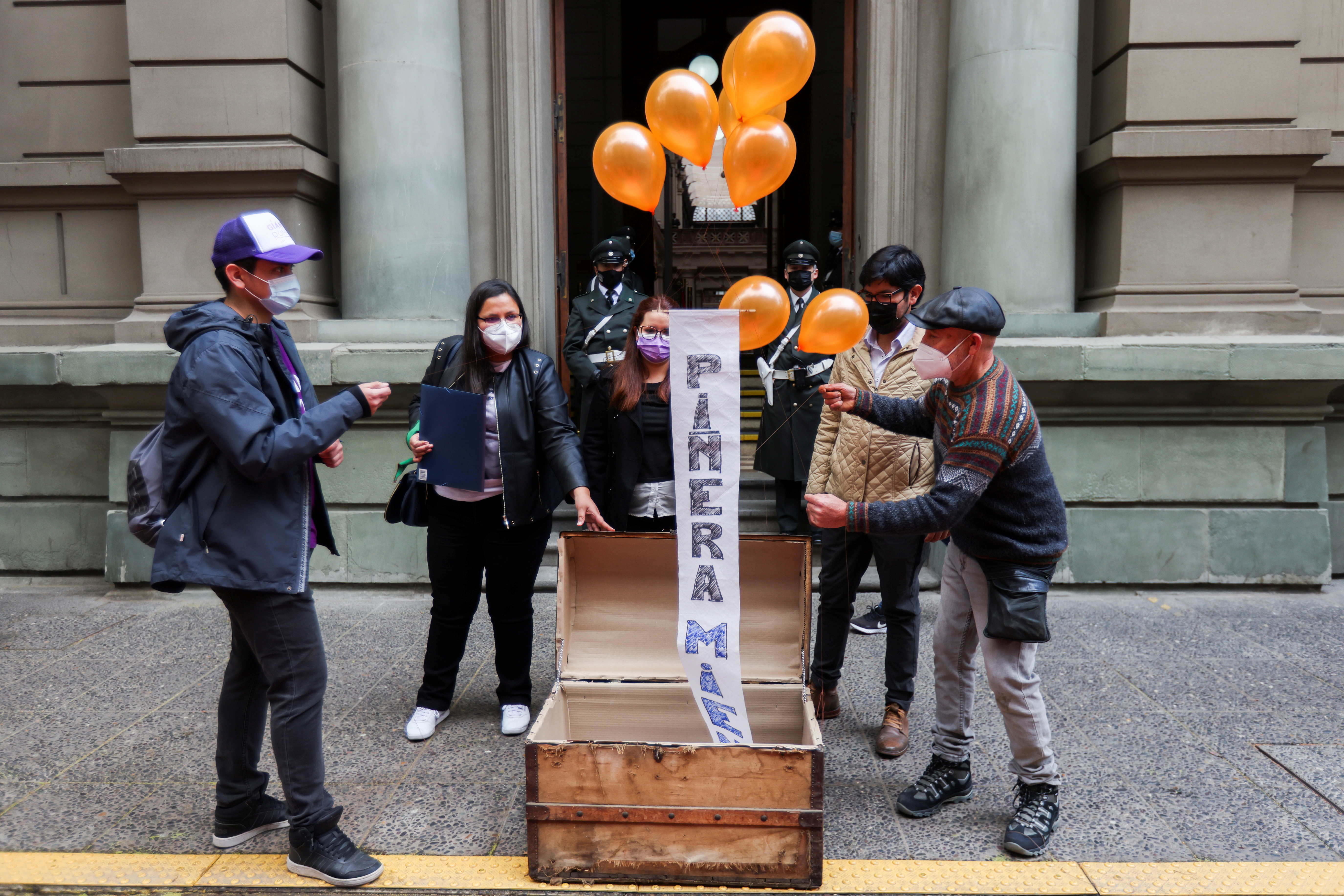 Demonstrators use balloons to lift a banner reading 'Pinera lies again' during a rally against Chile's President Sebastian Pinera , who according to the Pandora Papers investigation, used a tax haven to carry out the sale of the