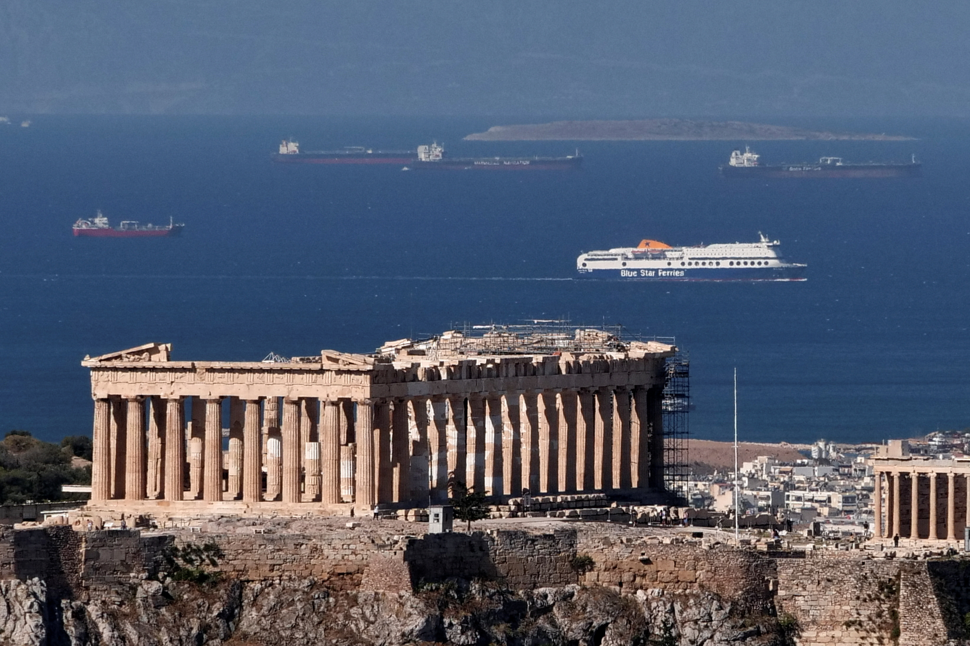 A view of the Parthenon temple atop the Acropolis hill as a passenger ferry sails in the background, a day before the official opening of the tourist season, in Athens, Greece, May 14, 2021. REUTERS/Vassilis Triandafyllou