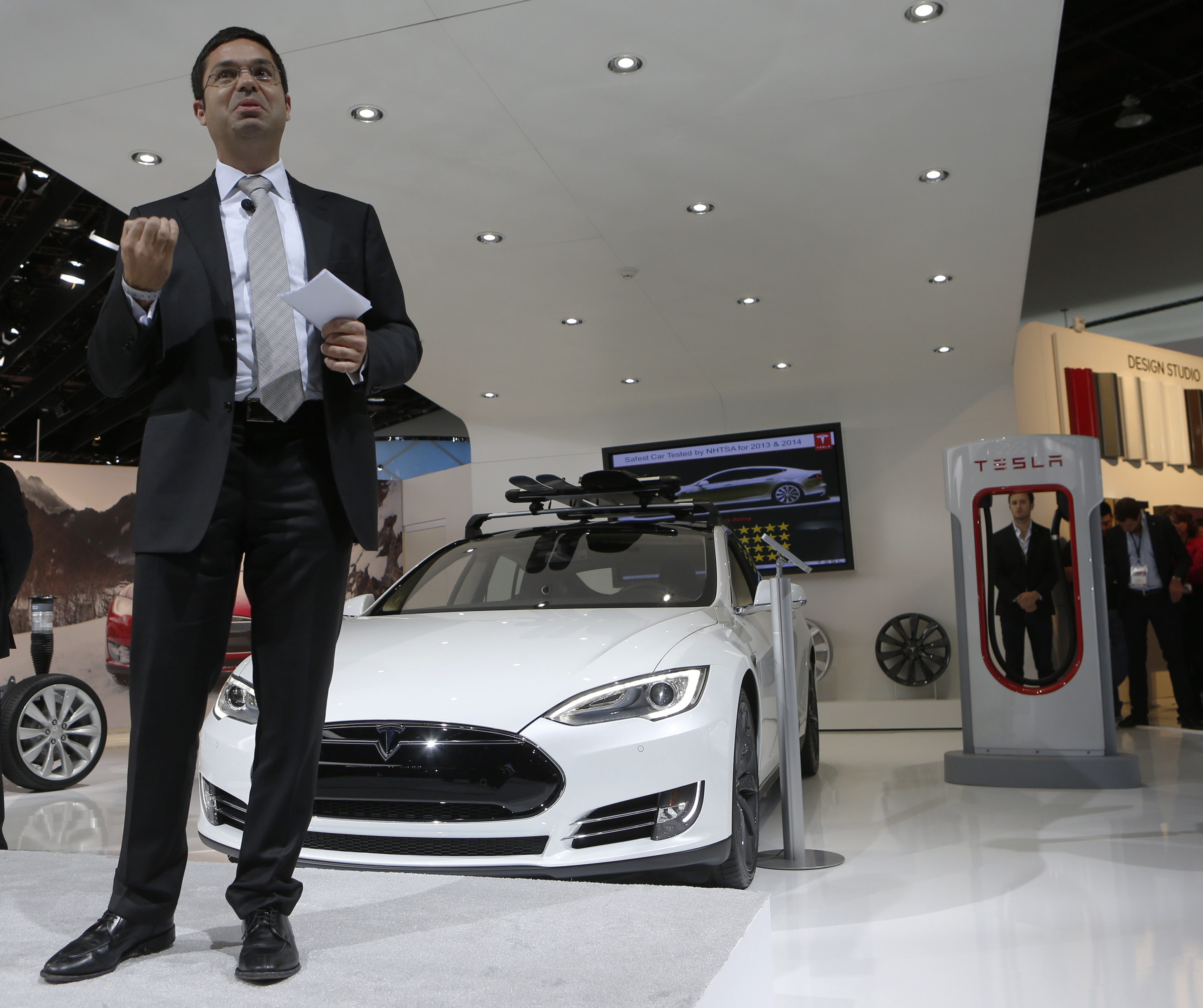 Jerome Guillen, Vice President of Tesla Sales and Service, speaks in front of a Tesla S electric car and a charging station (R) during the press preview day of the North American International Auto Show in Detroit, Michigan January 14, 2014. REUTERS/Rebecca Cook