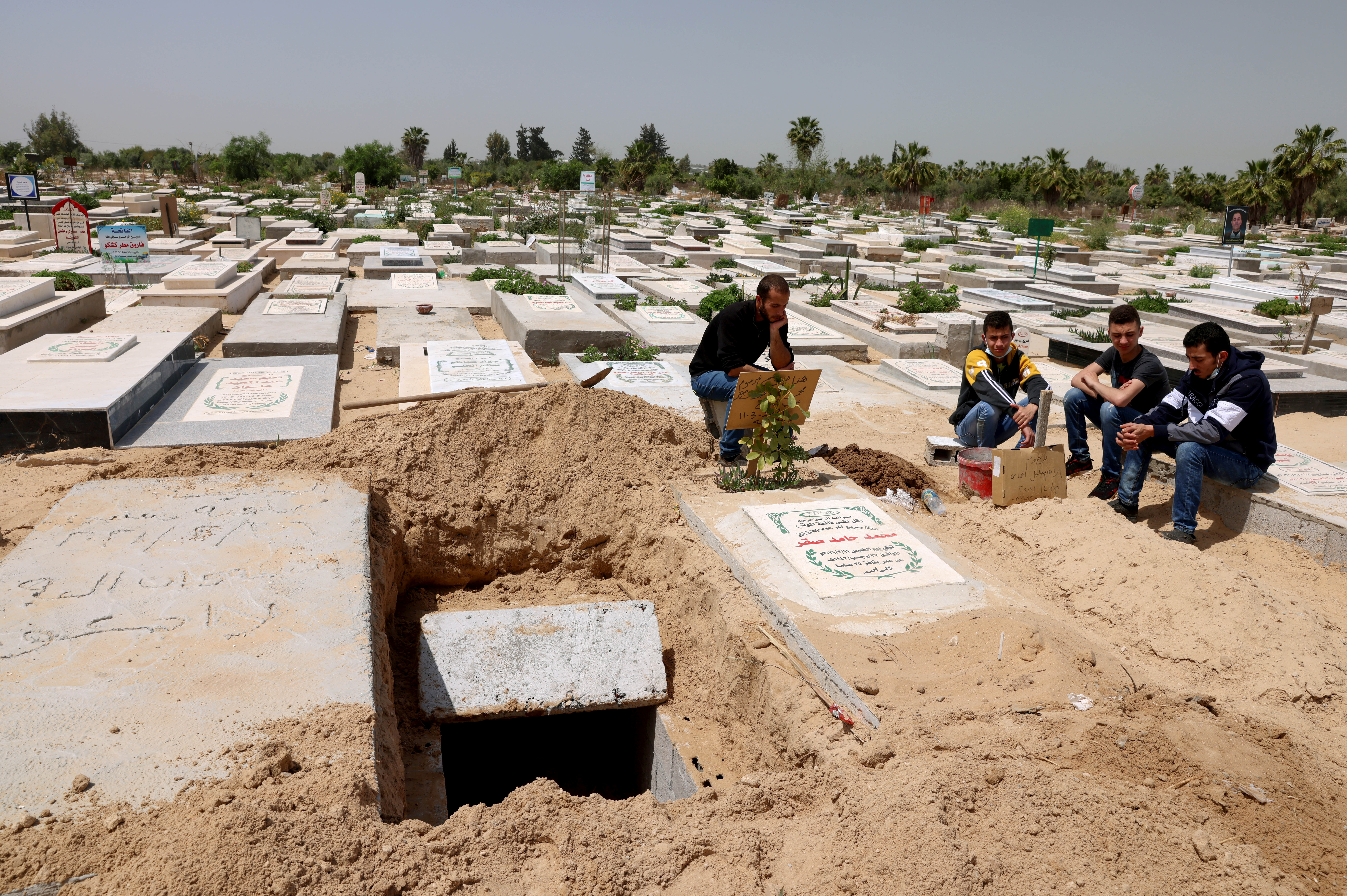 Palestinians wait to bury the body of their relative, who died after contracting the coronavirus disease (COVID-19), at a cemetery, east of Gaza City April 20, 2021. Picture taken April 20, 2021. REUTERS/Mohammed Salem