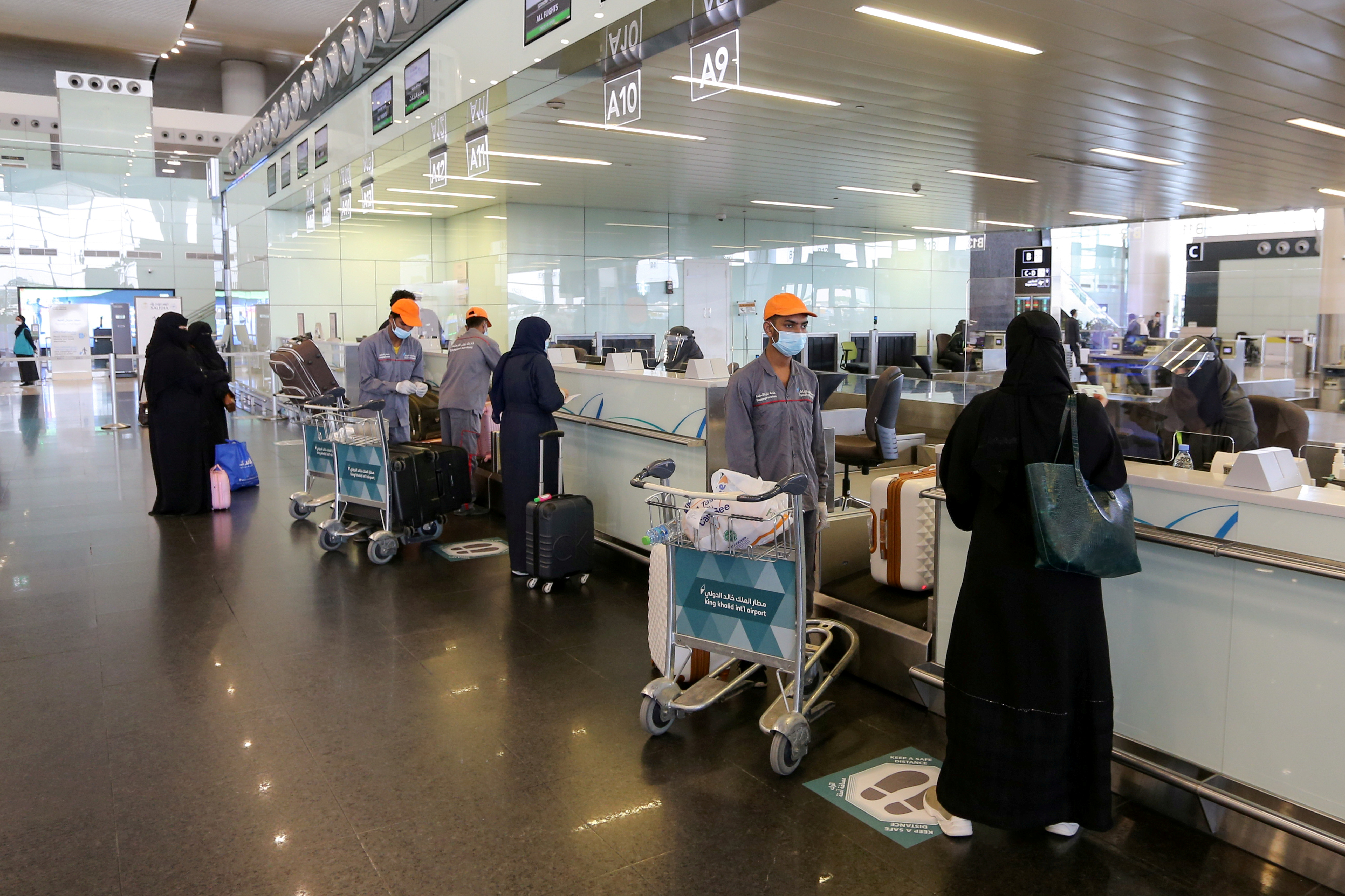 Passengers talk to airline employees at Riyadh International Airport, after Saudi Arabia reopened domestic flights, following the outbreak of the coronavirus disease (COVID-19), in Riyadh, Saudi Arabia May 31, 2020. REUTERS/Ahmed Yosri/File Photo