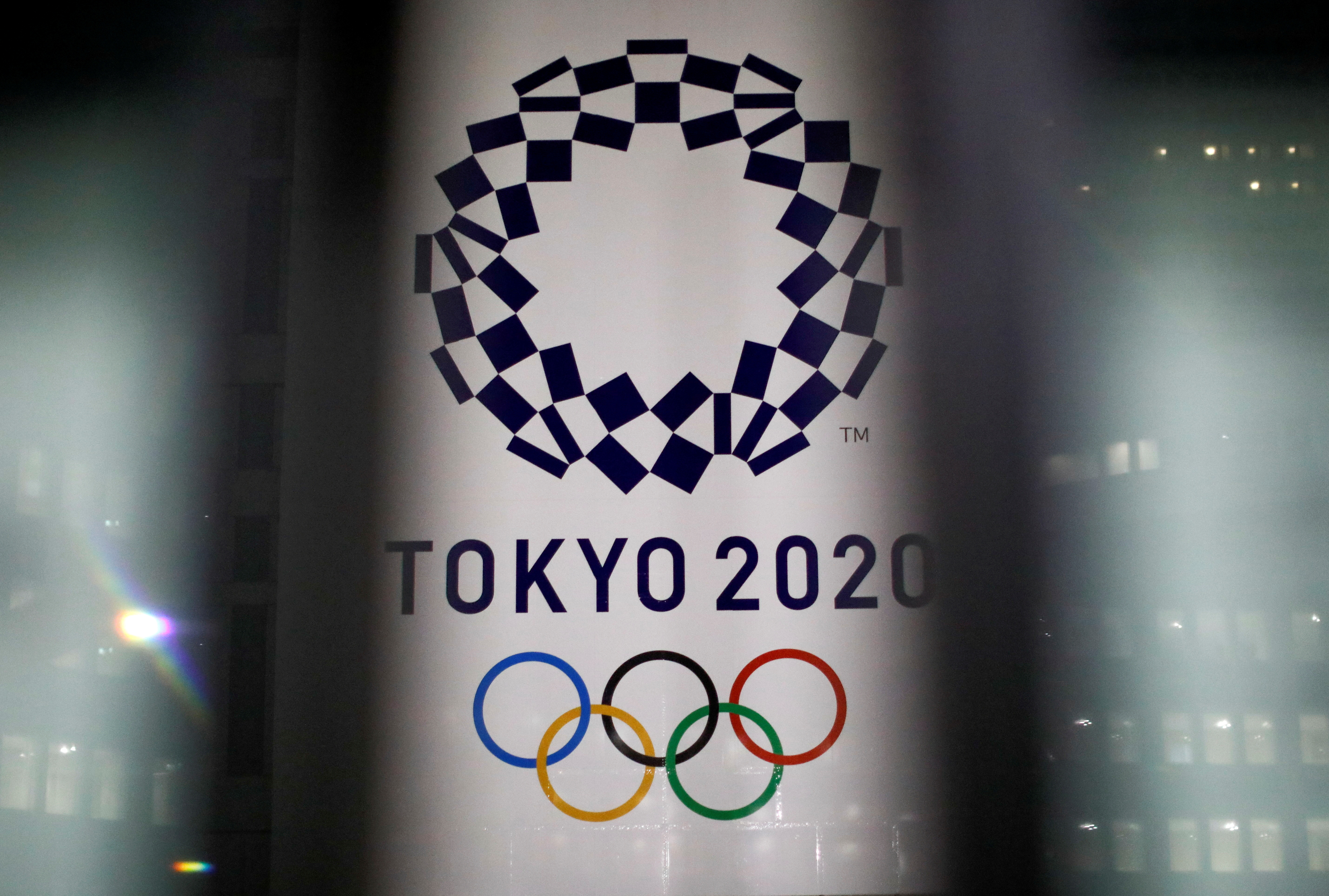 The logo of Tokyo 2020 Olympic Games that have been postponed to 2021 due to the coronavirus disease (COVID-19) outbreak, is seen through signboards, at Tokyo Metropolitan Government Office building in Tokyo, Japan January 22, 2021. REUTERS/Issei Kato/File Photo