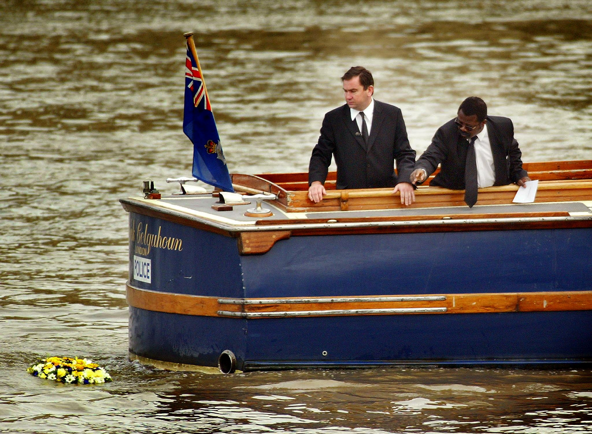 Detective Inspector Will O'Reilly (L) and John Azah of the Independent Advisory Group place a wreath in the River Thames at the place where the torso of a boy, who police have called 'Adam', was found a year ago, September 21, 2002. A minutes silence was observed at a memorial service held in City Hall before the wreath laying. REUTERS/Peter Macdiarmid/File Photo