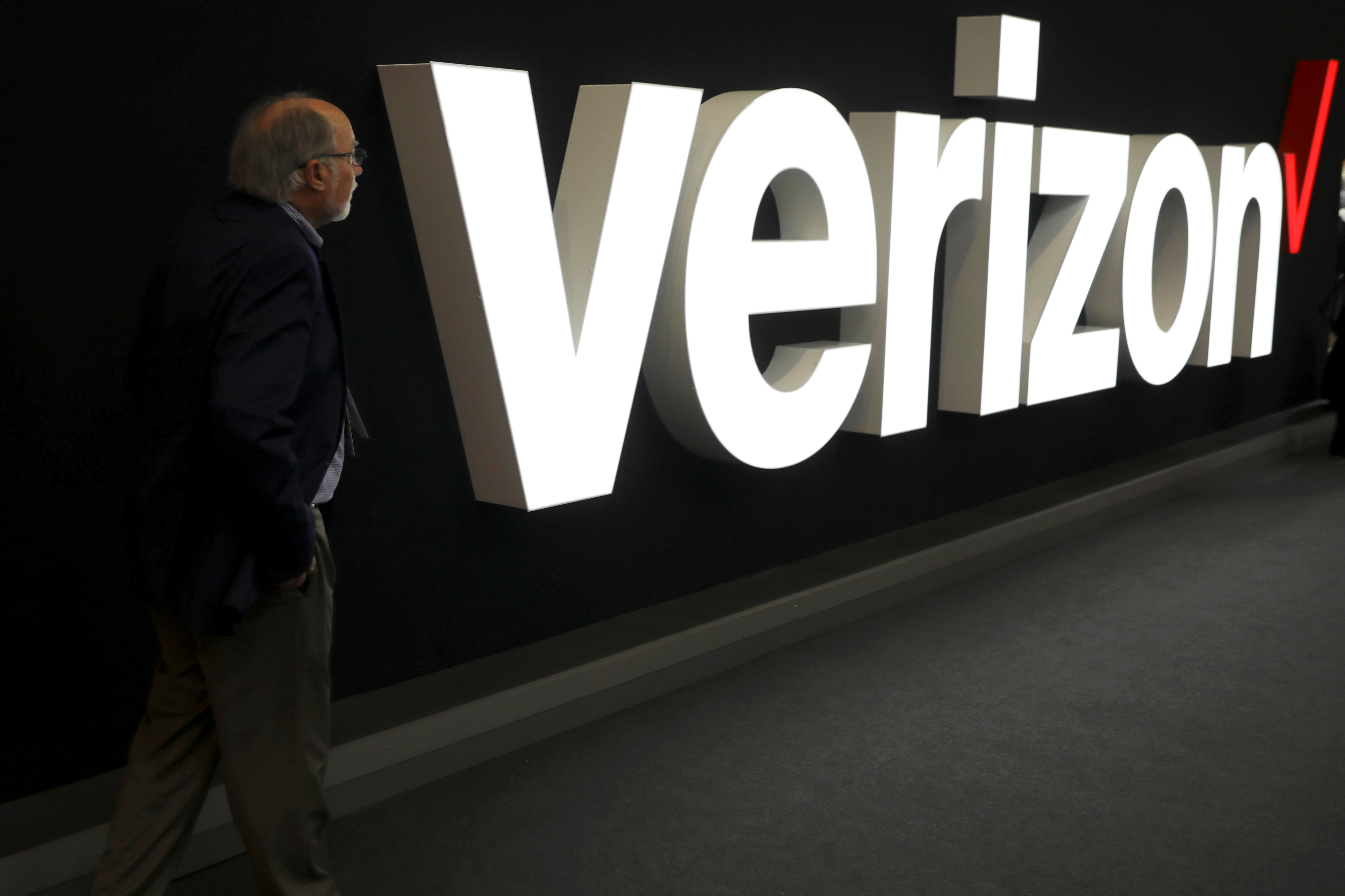 A man stands next to the logo of Verizon at the Mobile World Congress in Barcelona, Spain, February 26, 2019. REUTERS/Sergio Perez/File Photo