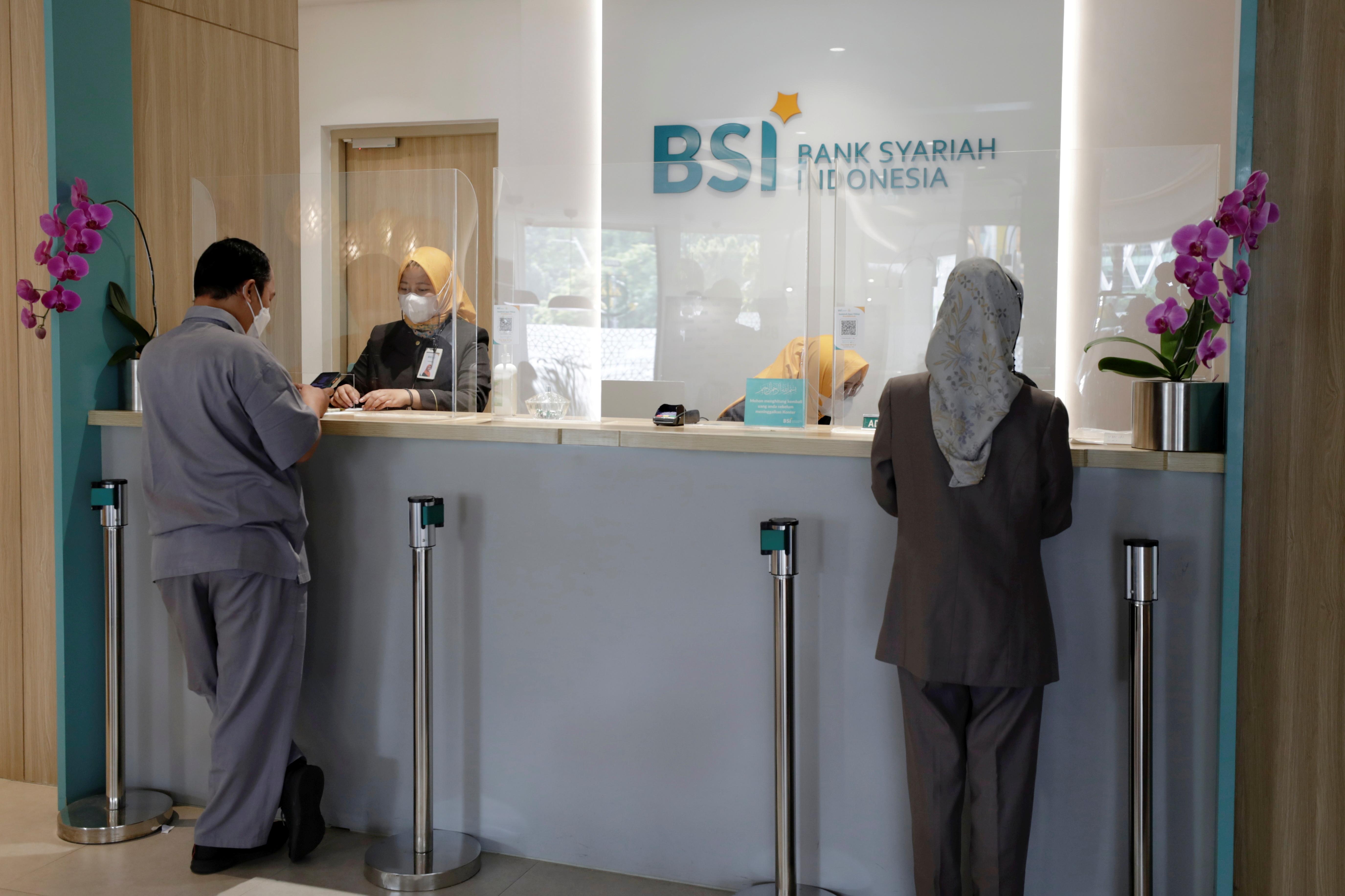Bank tellers serve customers at Bank Syariah Indonesia in Jakarta, Indonesia, June 8, 2021. REUTERS/Willy Kurniawan/File Photo