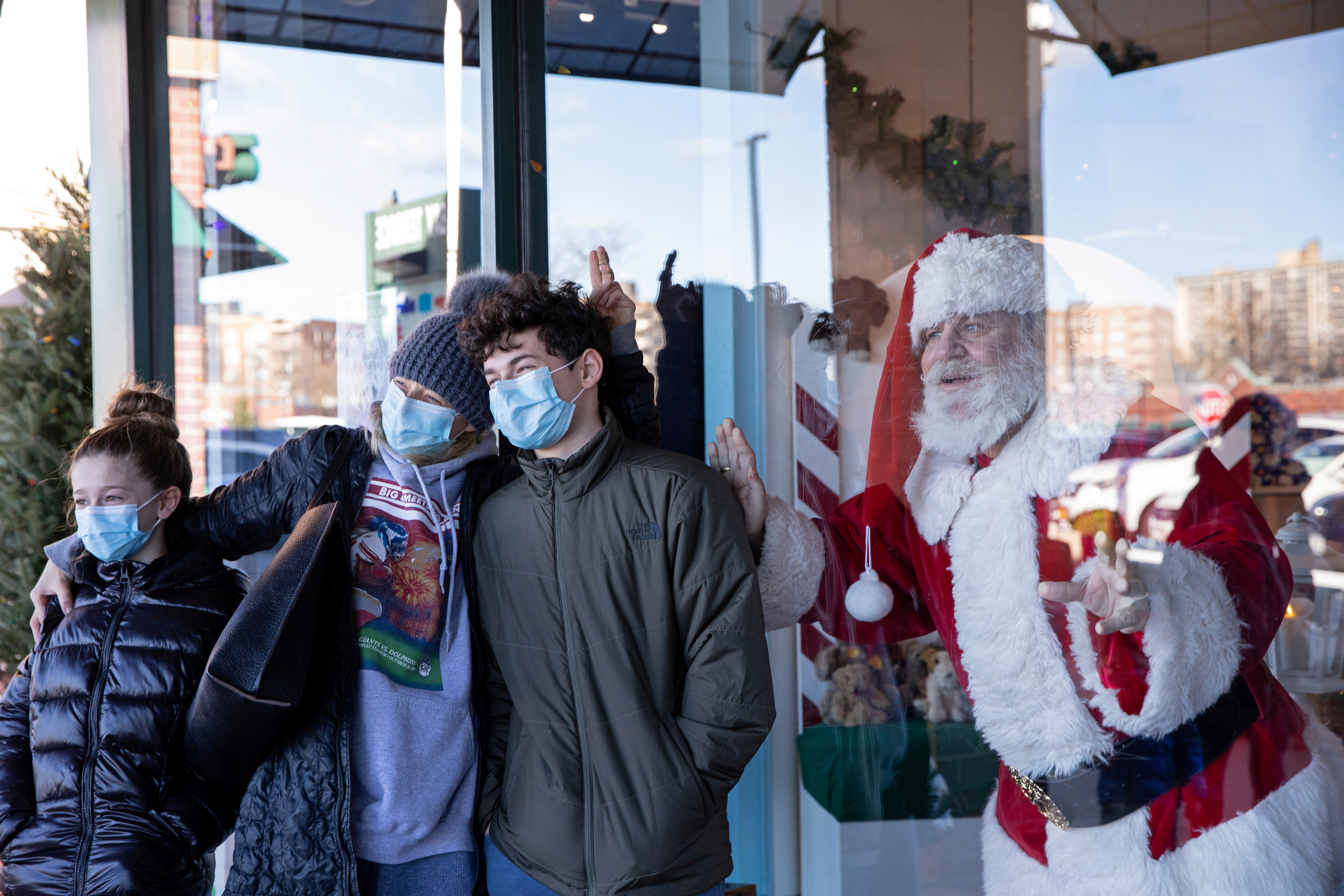 Dana Friedman, a trial lawyer who has spent 6 months of each year growing out his beard for his annual appearance as Santa Claus since 2001, poses for a portrait with a family through a window at the Bay Terrace Shopping Center in New York City, U.S., December 6, 2020. REUTERS/Caitlin Ochs