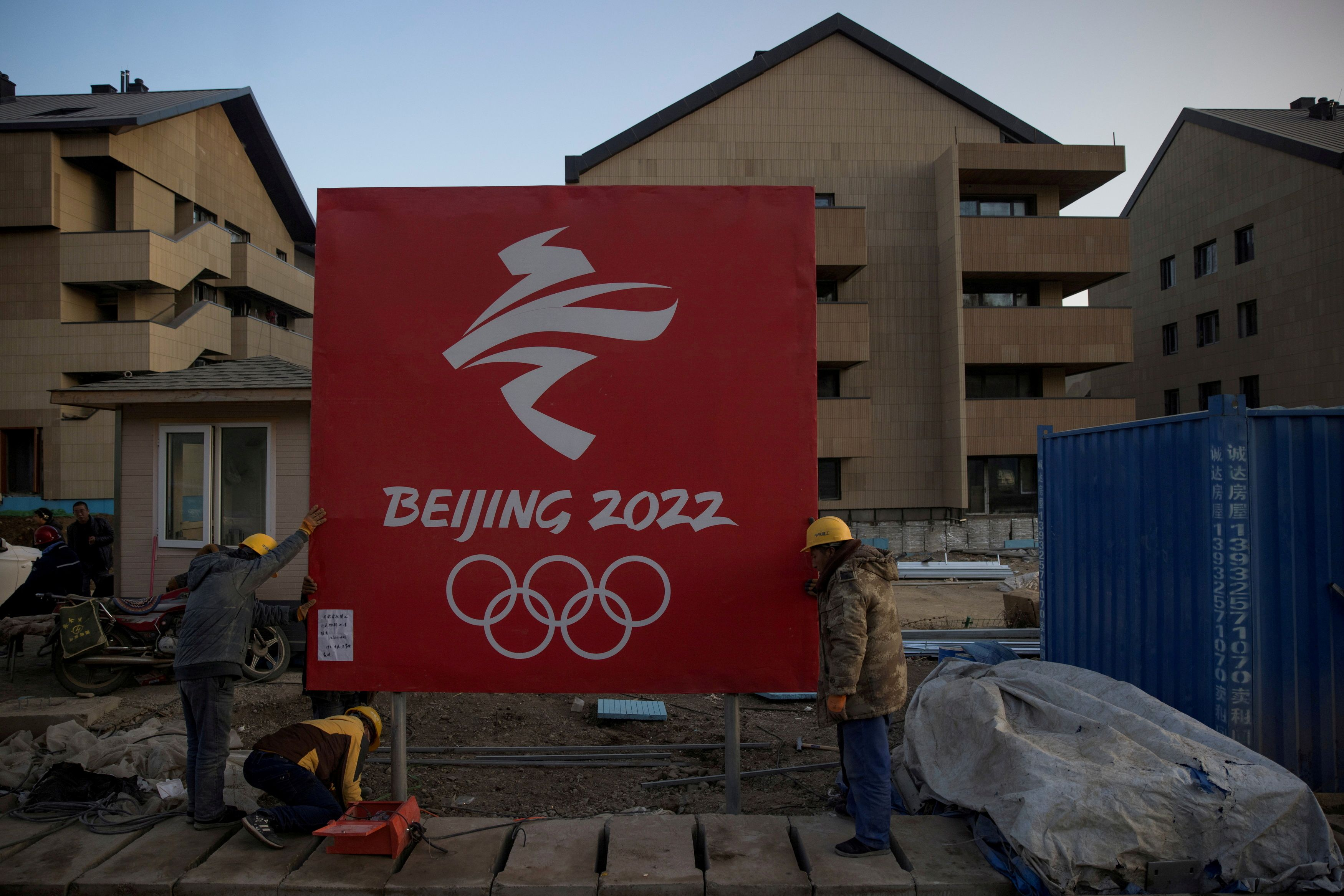 Workers move a sign at the Olympic Village for the 2022 Winter Olympics in the Chongli district of Zhangjiakou, Hebei province, China, October 29, 2020. REUTERS/Thomas Peter/File Photo