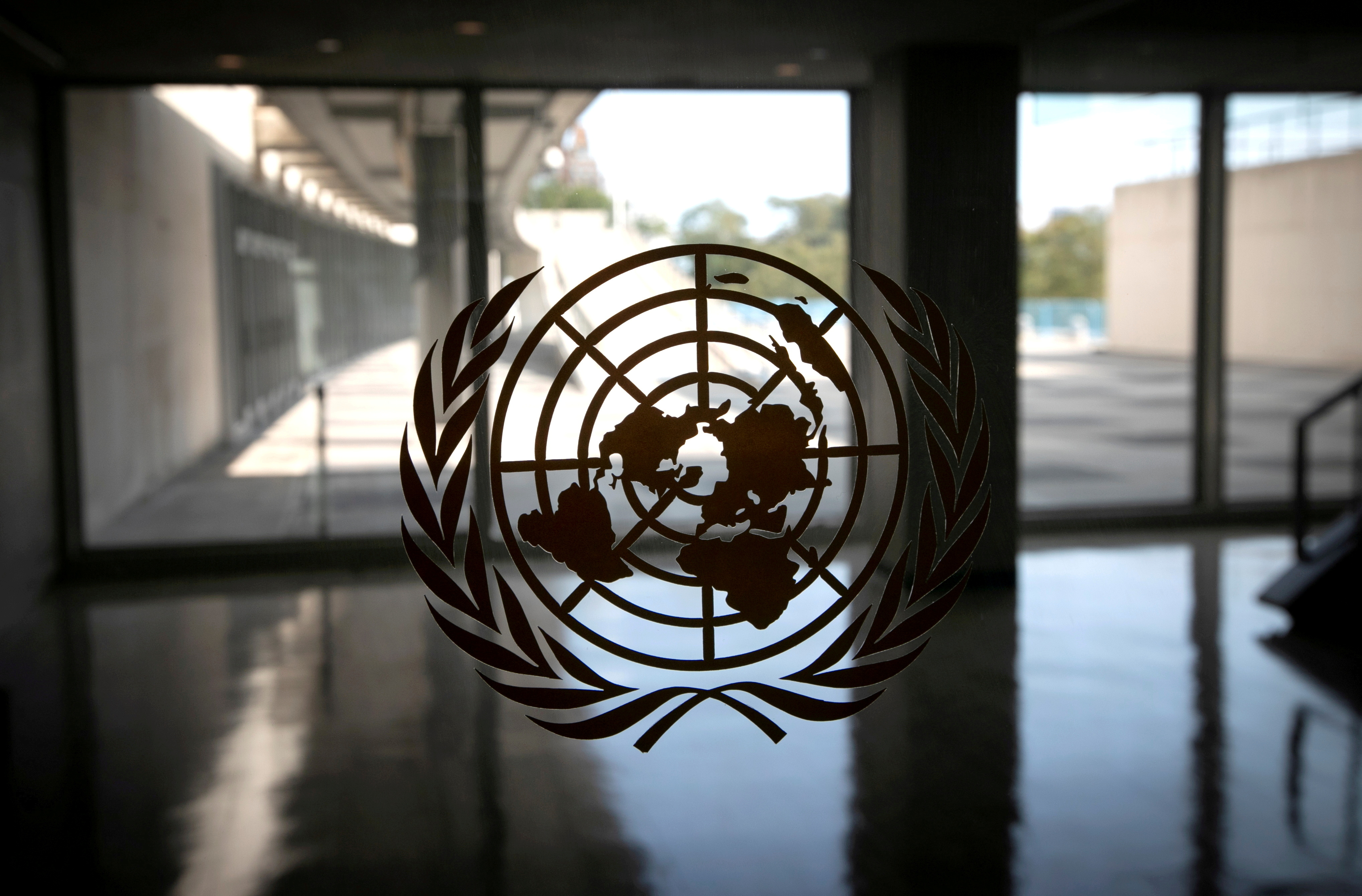 United Nations logo is seen on a window in an empty hallway at United Nations headquarters during the 75th annual U.N. General Assembly high-level debate in New York, U.S., September 21, 2020. REUTERS/Mike Segar/File Photo/File Photo