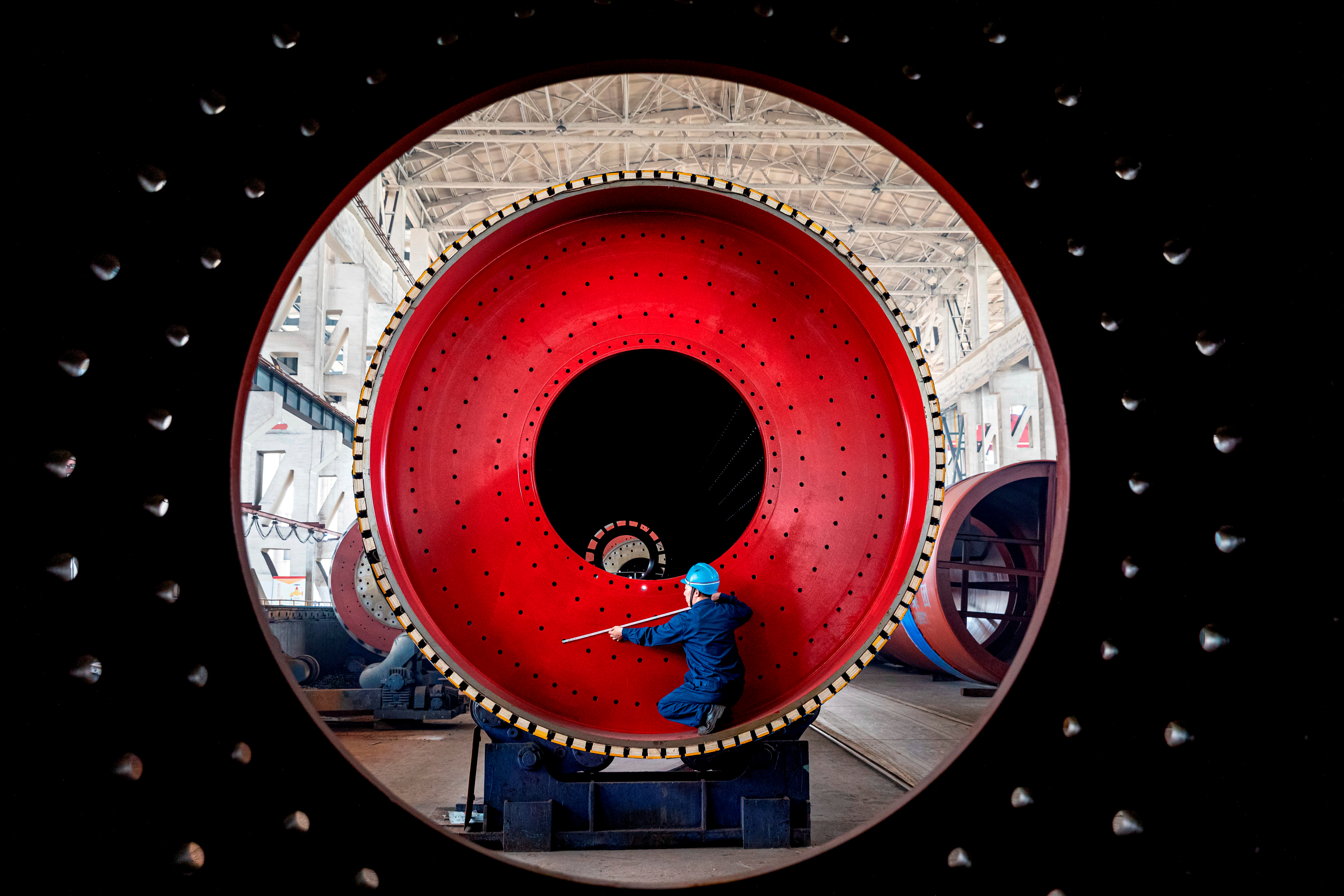 An employee measures a newly manufactured ball mill machine at a factory in Nantong, Jiangsu province, China June 28, 2019. REUTERS/Stringer/File Photo