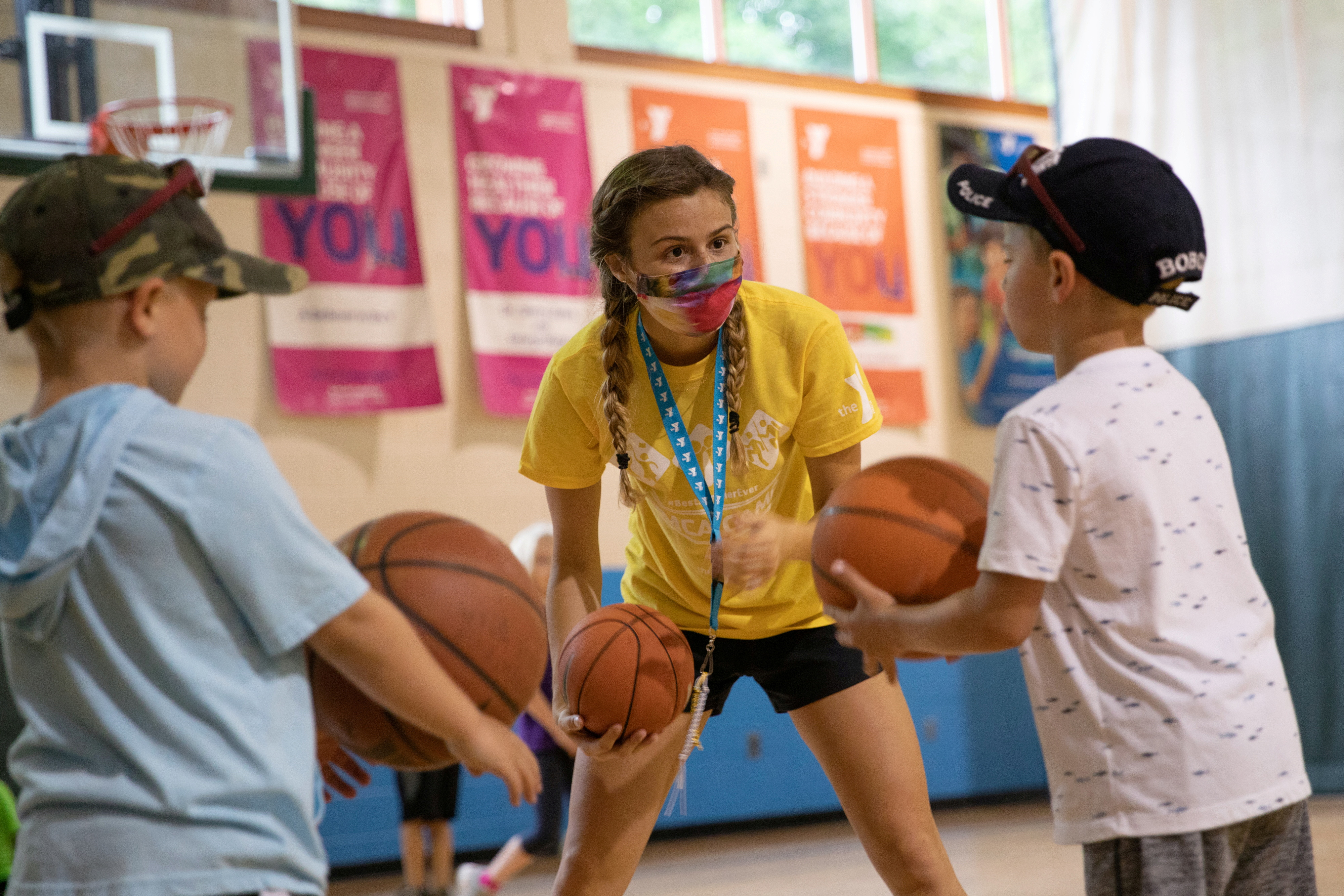 A counselor wearing a protective face mask plays with children as summer camps reopen amid the spread of coronavirus disease (COVID-19) at Carls Family YMCA summer camp in Milford, Michigan, U.S., June 23, 2020.  REUTERS/Emily Elconin