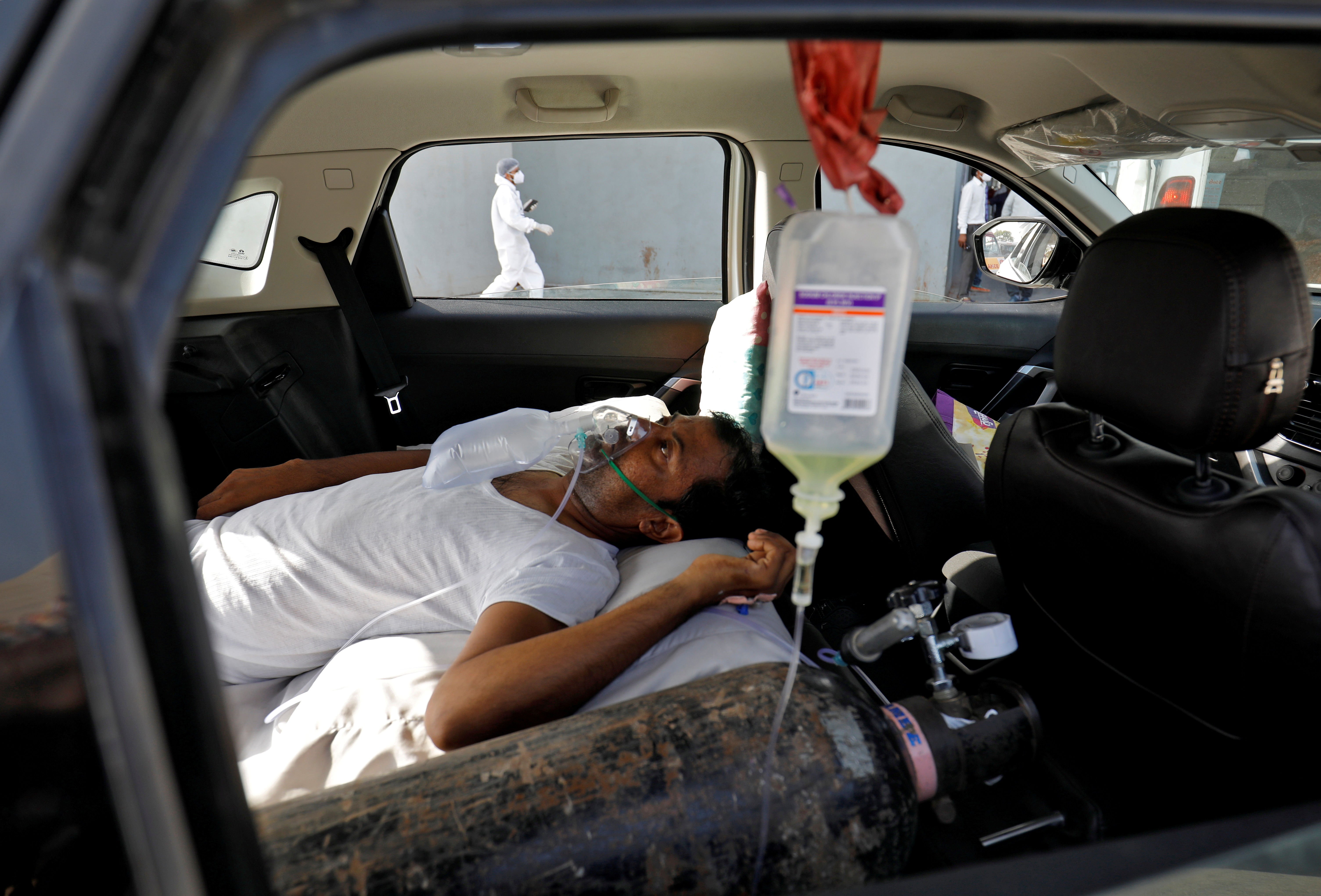 A patient with breathing problems lies inside a car while waiting to enter a COVID-19 hospital for treatment, amidst the spread of the coronavirus disease (COVID-19), in Ahmedabad, India, April 22, 2021. REUTERS/Amit Dave