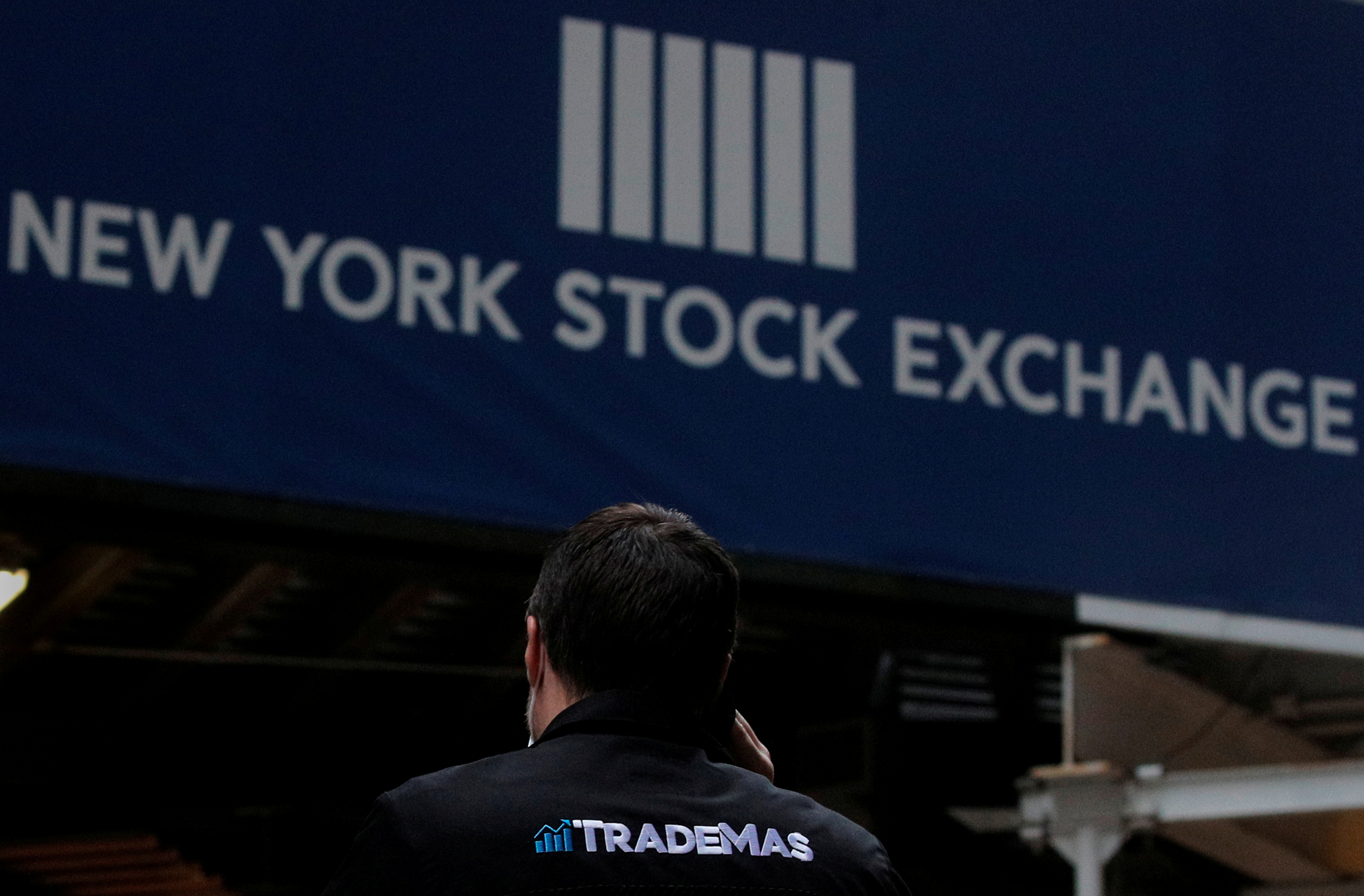 Trader Frank Masiello talks on his phone on Wall St. outside the New York Stock Exchange (NYSE) in New York, U.S., January 15, 2021. REUTERS/Brendan McDermid/File Photo