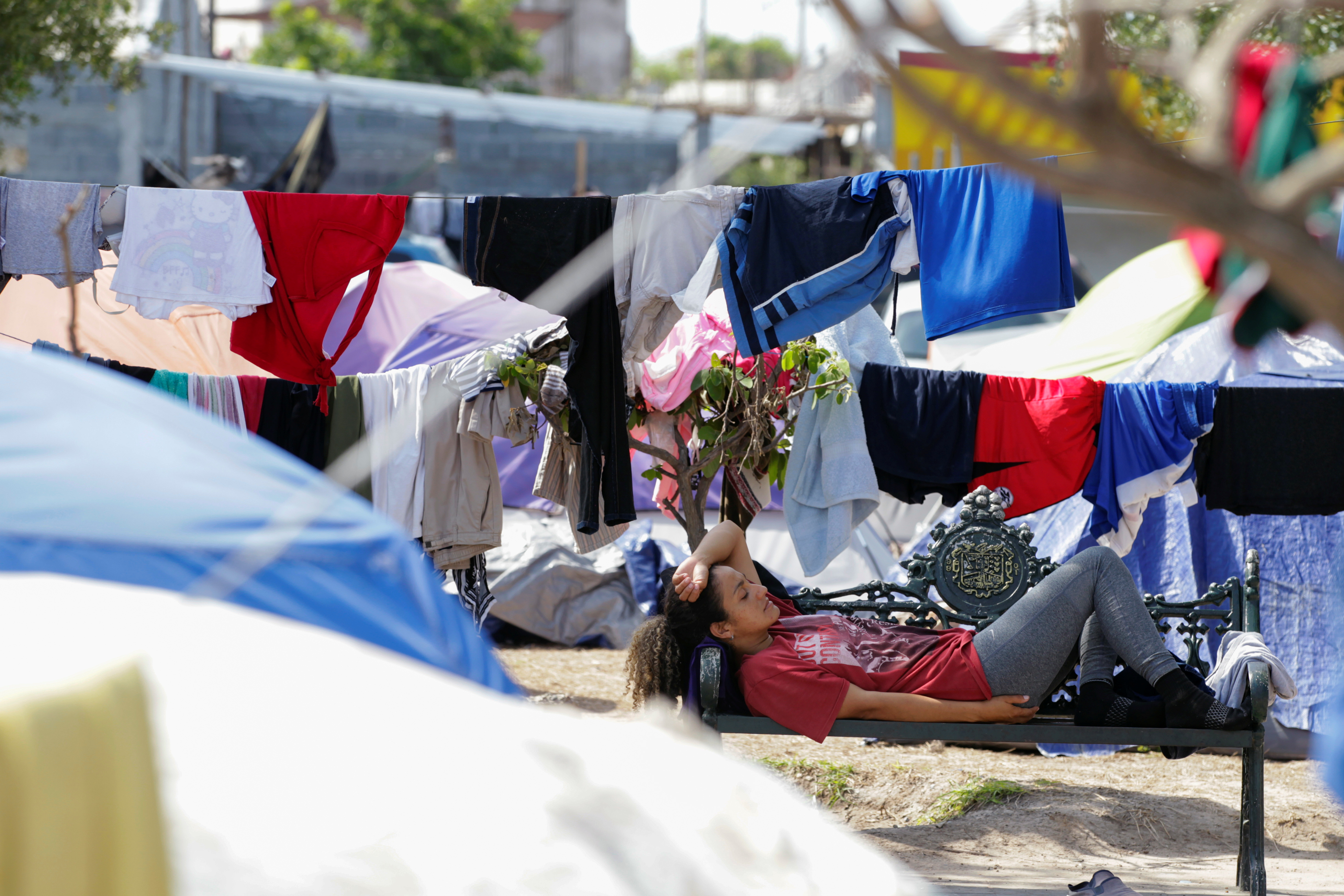 An asylum-seeking migrant, who was apprehended and returned to Mexico under Title 42 after crossing the border from Mexico into the U.S., rests in a public square where hundreds of migrants live in tents, in Reynosa, Mexico June 9, 2021. Picture taken June 9, 2021. REUTERS/Daniel Becerril