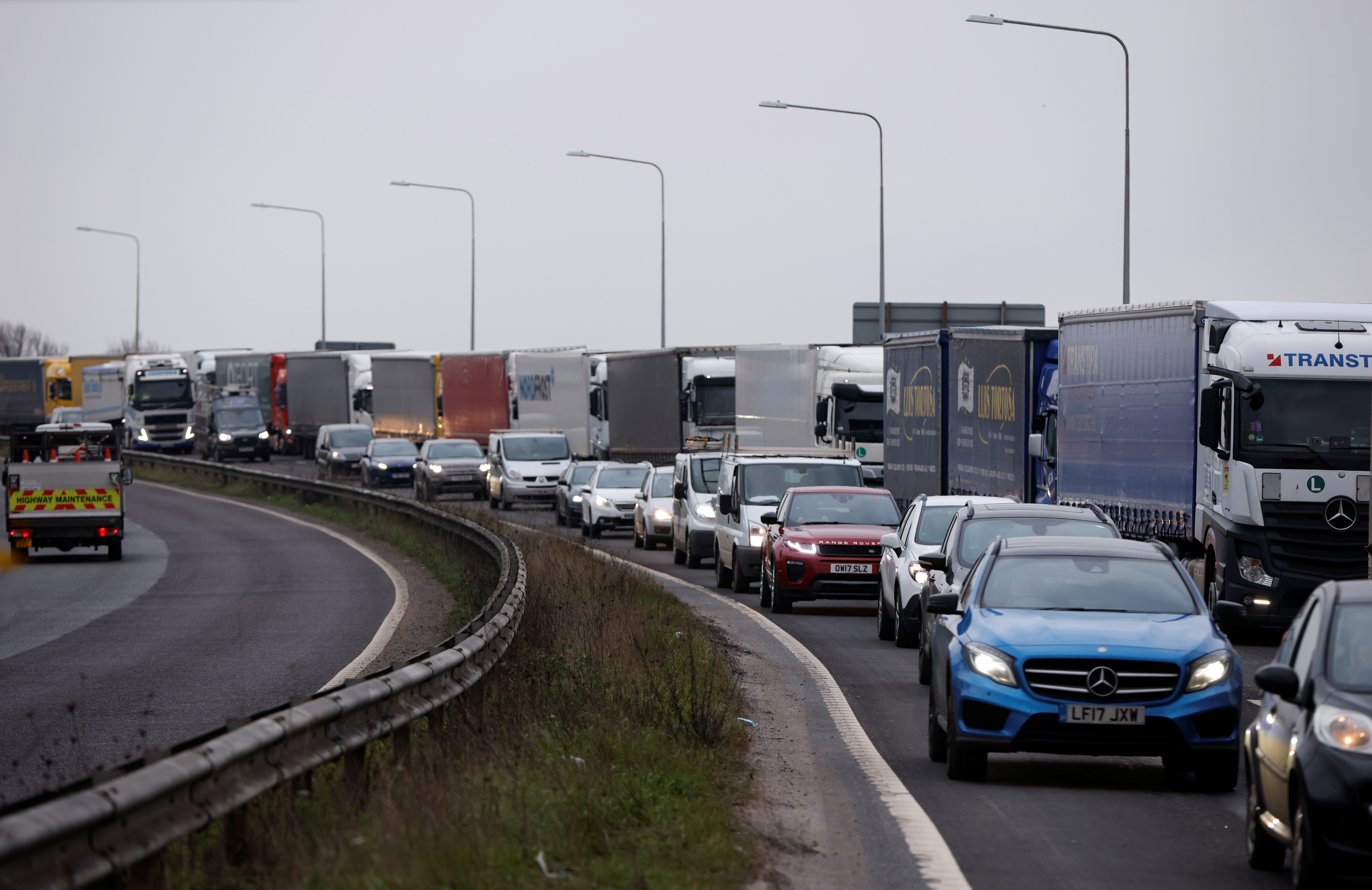 Trucks queue on the road leading to the Waterbrook Inland Border Facility, a temporary customs clearance centre set up in a truck stop in Ashford, Kent, Britain January 15, 2021. REUTERS/John Sibley