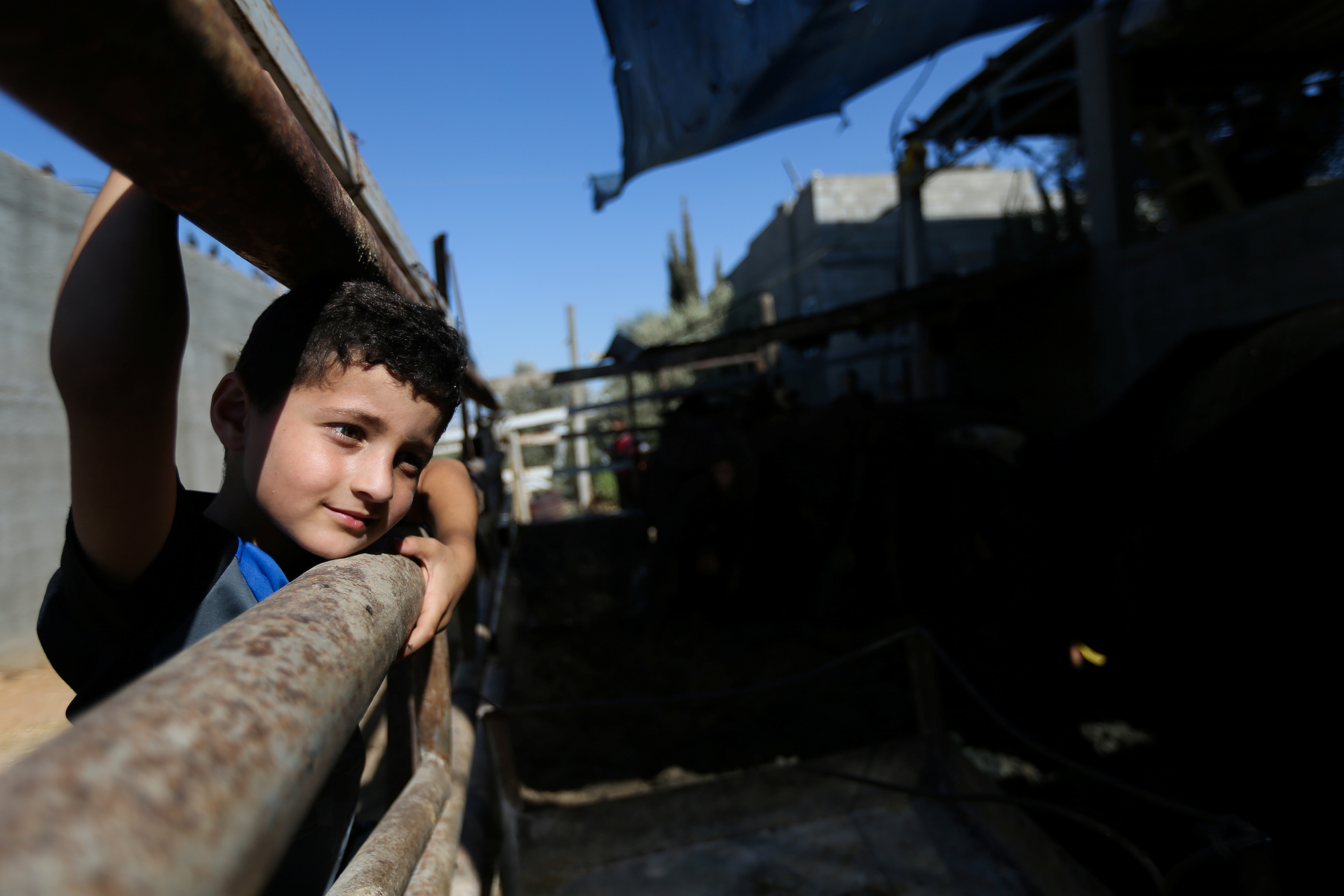 Palestinian boy Adam Issa looks on at a cow farm, in the central Gaza Strip July 14, 2021. Picture taken July 14, 2021. REUTERS/Ibraheem Abu Mustafa