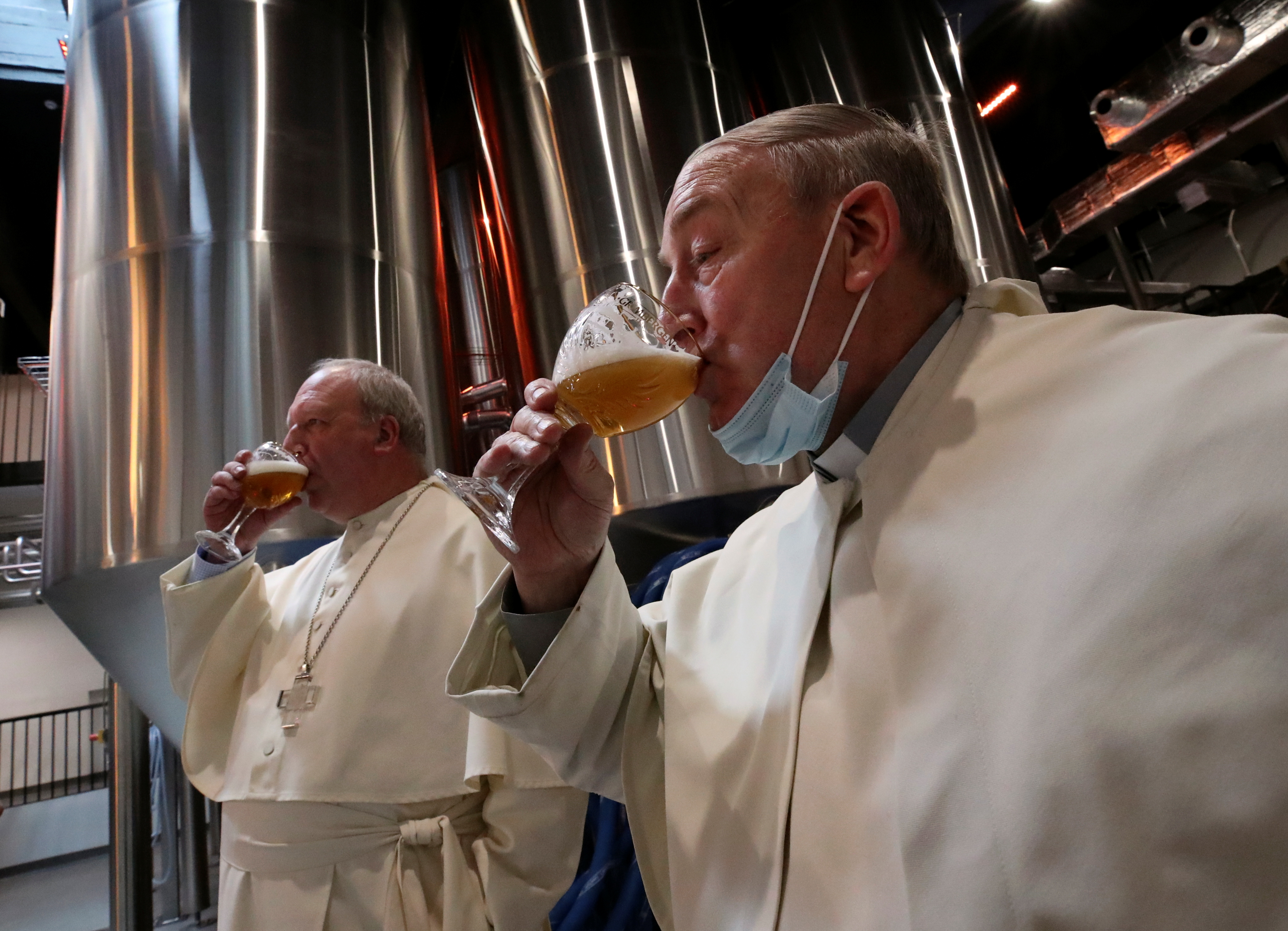Abbot Erik De Sutter and father Stefaan Verstraeten taste beer after blessing beer tanks at the Belgian Abbey of Grimbergen, which returns to brewing after a break of more than 200 years with a new microbrewery in Grimbergen, Belgium May 26, 2021. REUTERS/Yves Herman